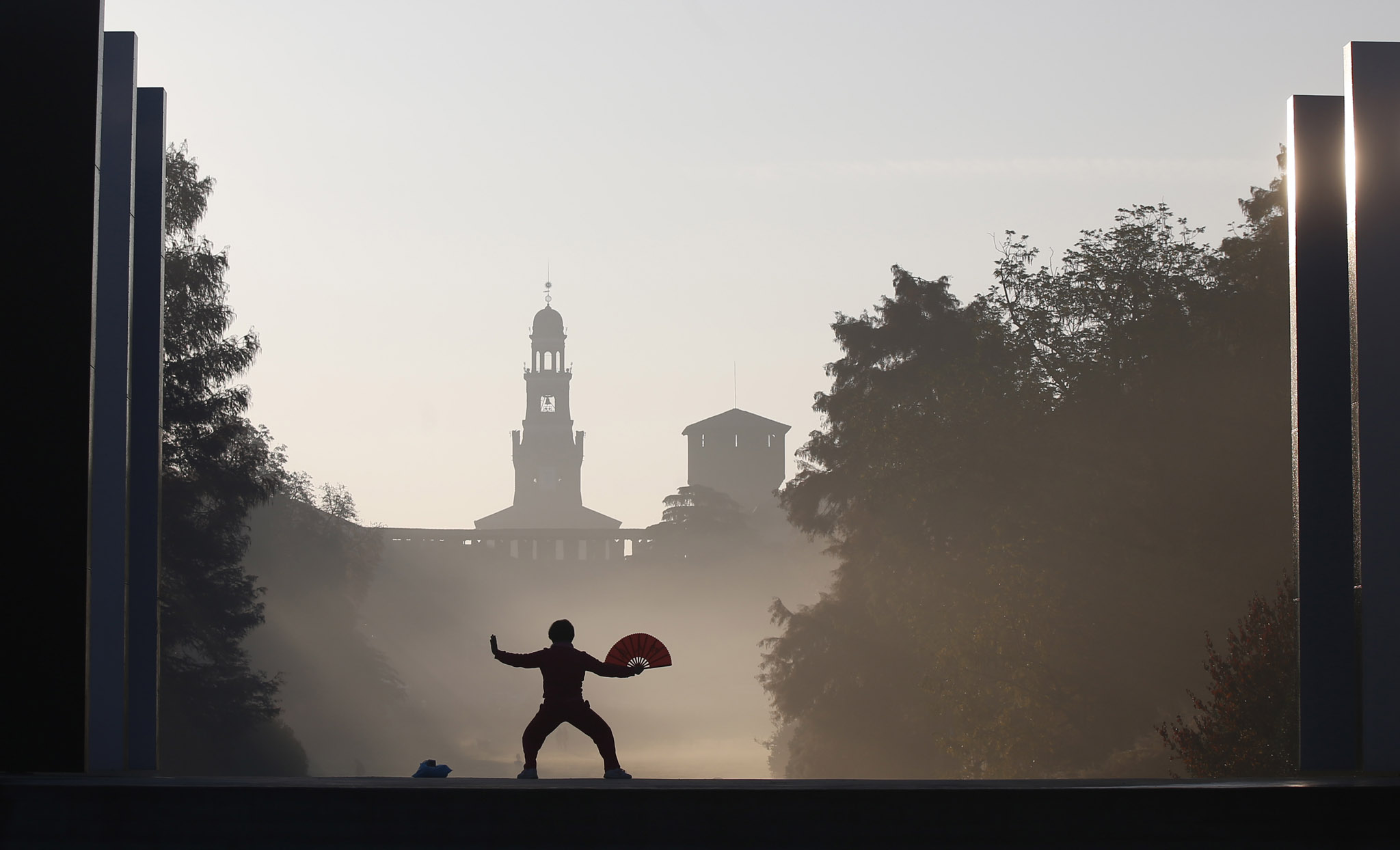 A woman practices Tai-Chi in front of the Sforzesco Castle at the Sempione park in Milan, Italy