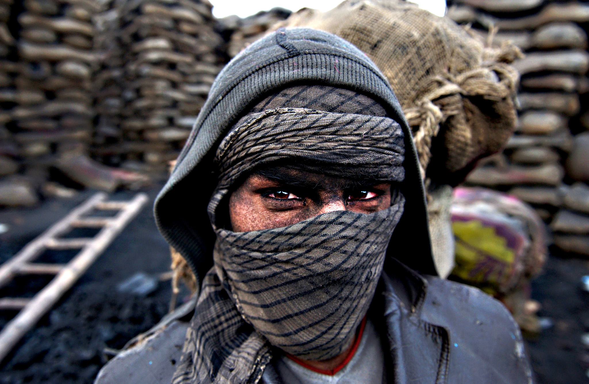 An Afghan worker walks next to coal blocks to be crushed and sold as fuel source during winters in Kabul, Afghanistan, on Wednesday