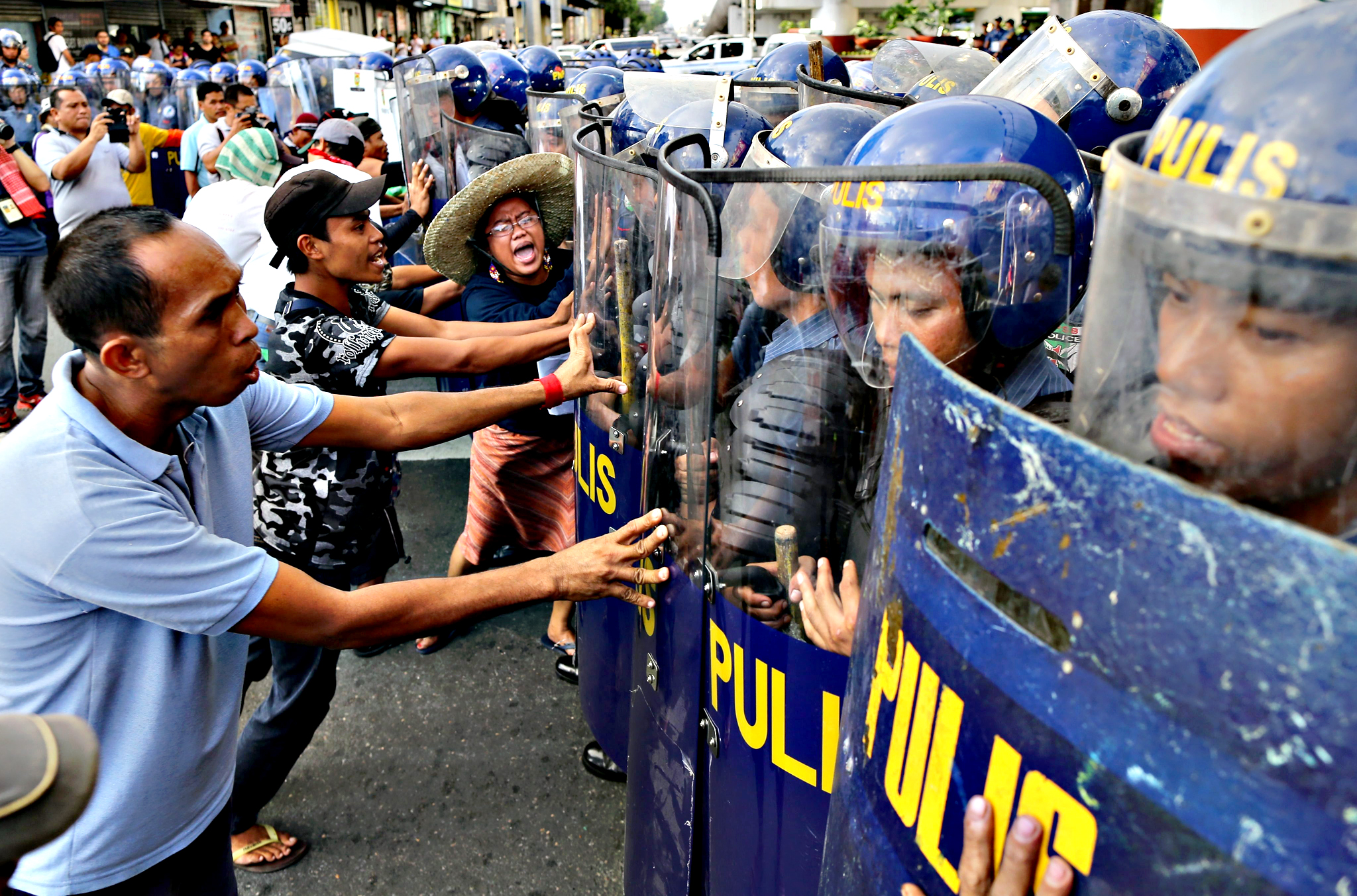 Filipino activists scuffle  with anti-riot police during a protest rally against the Asia-Pacific Economic Cooperation (APEC) in Manila, Philippines, 16 November 2015. According to the statement of the protesters, they blamed the APEC on the collapse of local business, low wages and environmental degradation. The Philippines will hosts the summit on 18 and 19 November.
