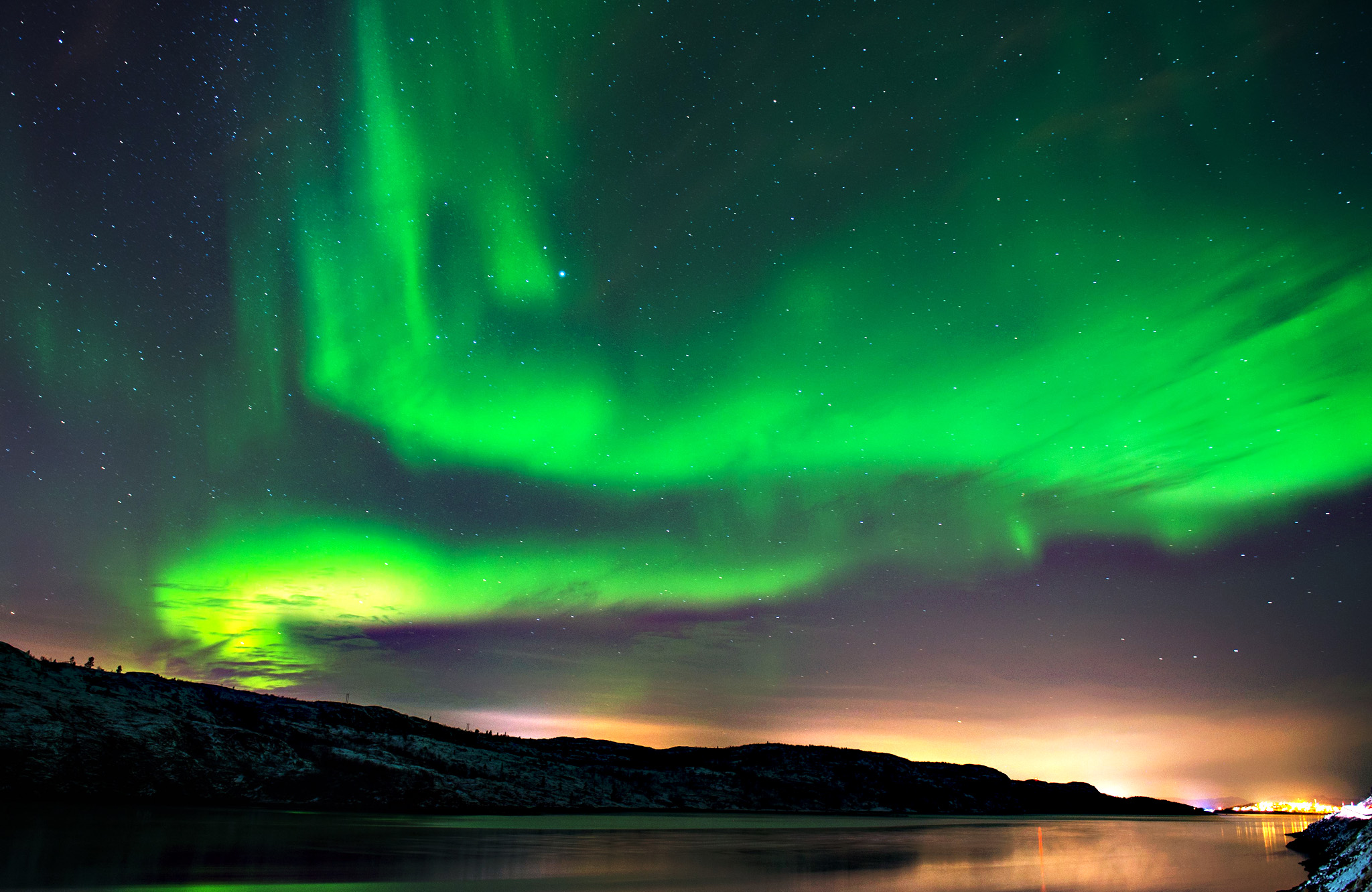 The Aurora Borealis or Northern Lights illuminate the night sky near the town of Kirkenes in northern Norway.