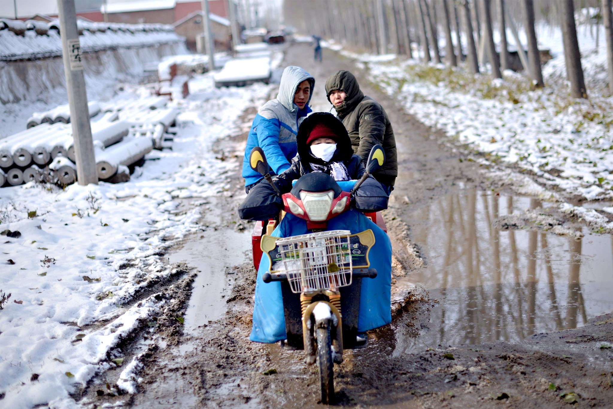 A group of men ride a tricycle across a muddy road in Beijing on Monday
