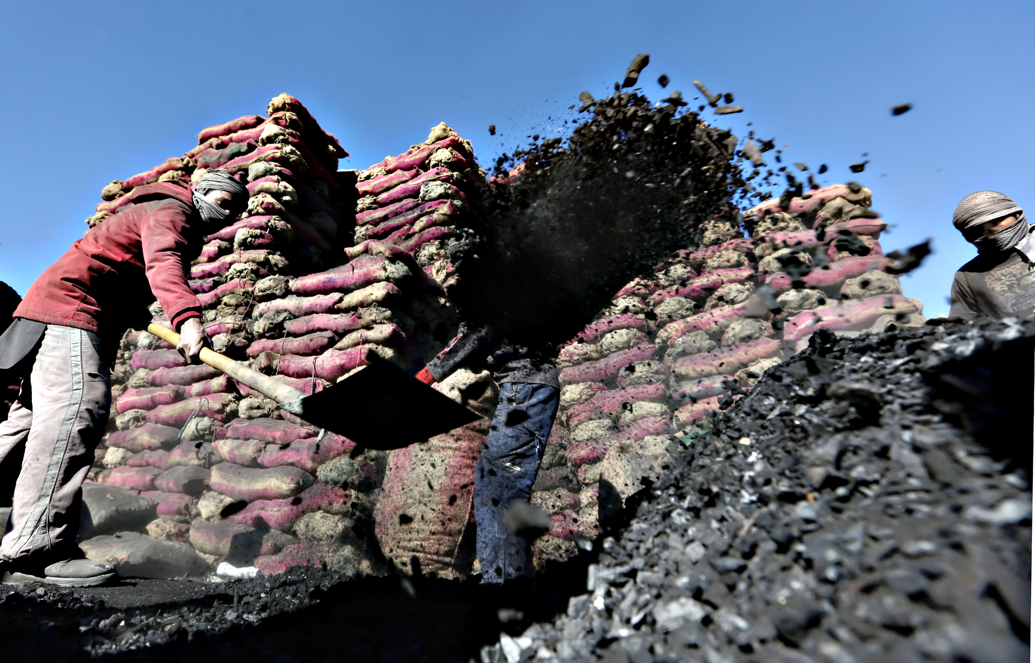 Afghan laborers work at a charcoal shop in Kabul, Afghanistan, Monday, Nov. 16, 2015. In the winter, prices of wood and charcoal rise among all other necessities for Afghans.