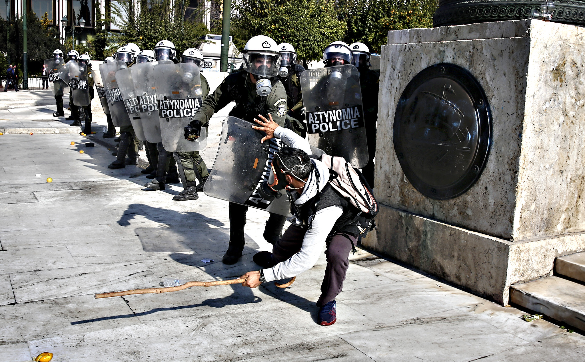 A farmer tries to protect himself as he clashes with a riot policeman during an anti-government protest at central Syntagma square in Athens, Wednesday, Nov. 18, 2015. Greek farmers protesting over planned tax and pension reforms demanded by the country's bailout creditors have clashed outside parliament with police, who used tear gas to disperse them.