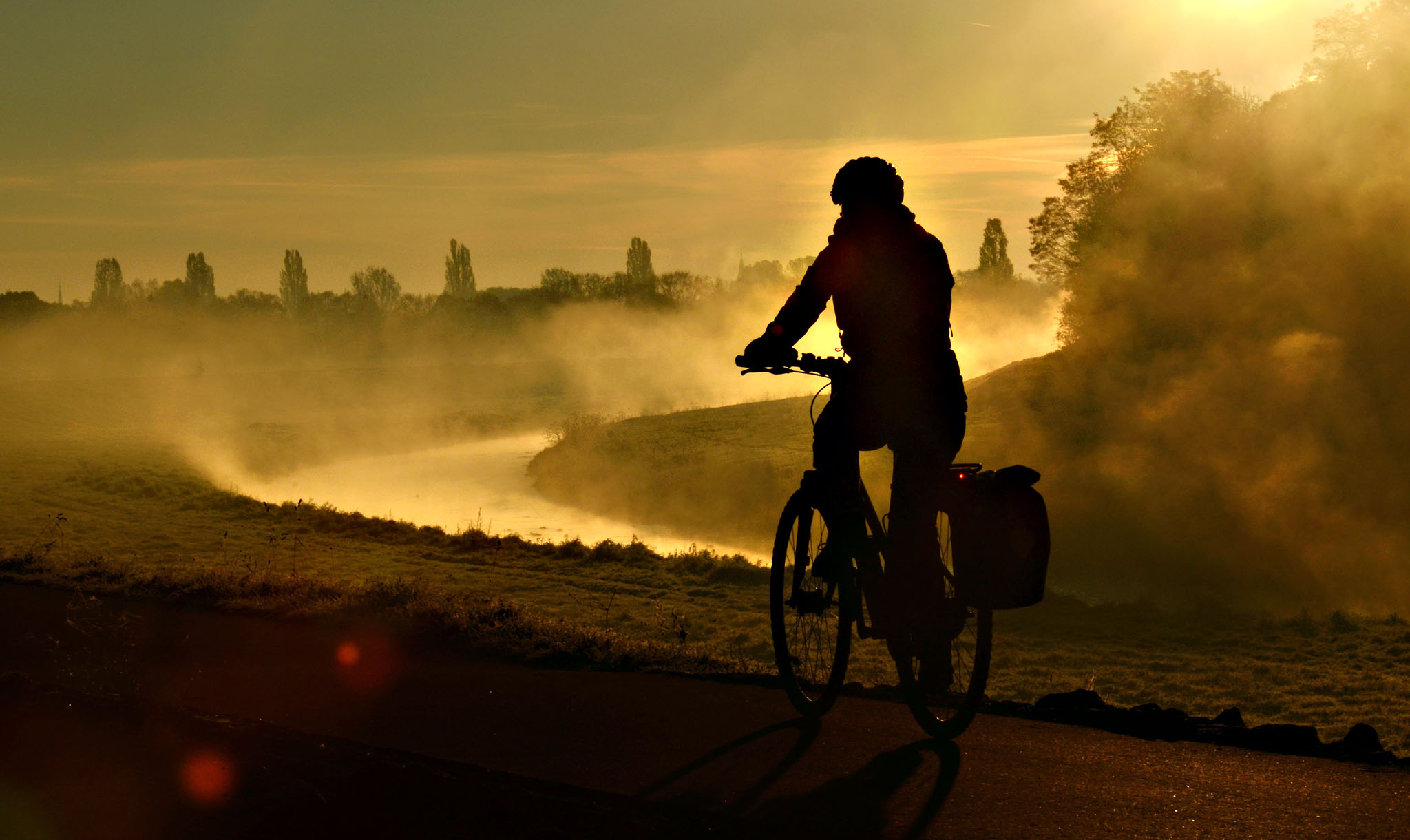 A cyclist drives past wafts of mist rising from a tributary of the Weisse Elster river in Leipzig, eastern Germany, on Tuesday