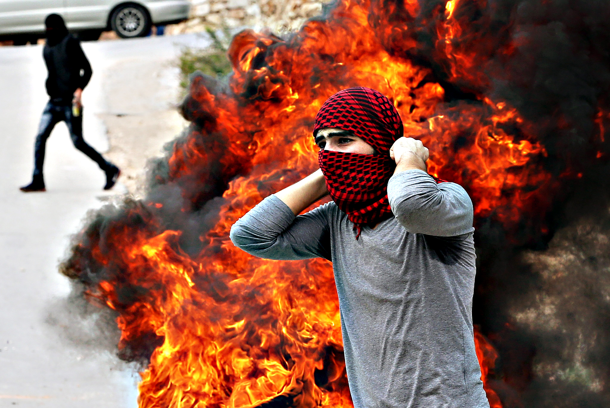 Palestinian protesters fuel a burning barricade of tires during clashes with Israeli security forces in the West Bank city of Hebron, 06 November 2015. Palestinians have launched dozens of knife attacks against Israelis since early October, avenging perceived Israeli violations, denied by Israel, at al-Aqsa Mosque in Jerusalem. Israel has retaliated against Palestinian protesters hurling petrol bombs and rocks with tear gas, rubber bullets and also live ammunition, as well as undercover commandos.