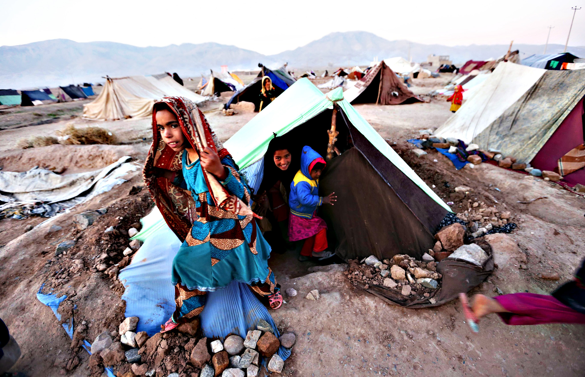 Afghan children displaced from Faryab, Badghis and Ghor province, stand outside a temporary shelter at an Internally Displaced Persons (IDPs) camp in Herat, Afghanistan, on Thursday. According to UN Refugee Agency (UNHCR) figures, the number of internally displaced Afghani people was 683,000 by mid-2014, estimating they will amount to 900,000 by the end of 2015.