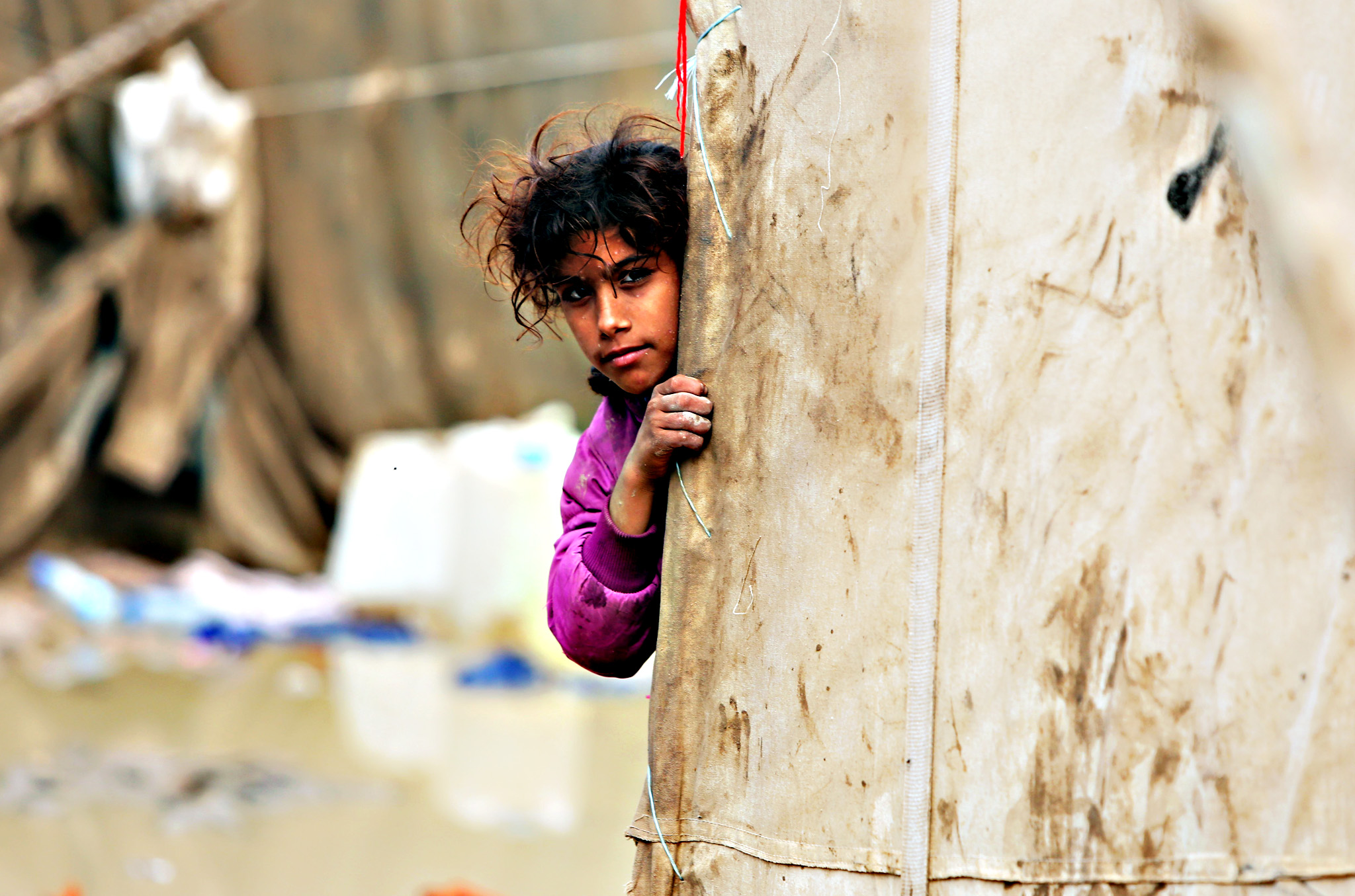 A displaced Iraqi girl looks out from behind a tent at a camp in Baghdad following heavy rainfall on November 5, 2015. Torrential rain caused chaos across several parts of Iraq last week, with flood waters sweeping the capital causing flooding, deaths and property destruction