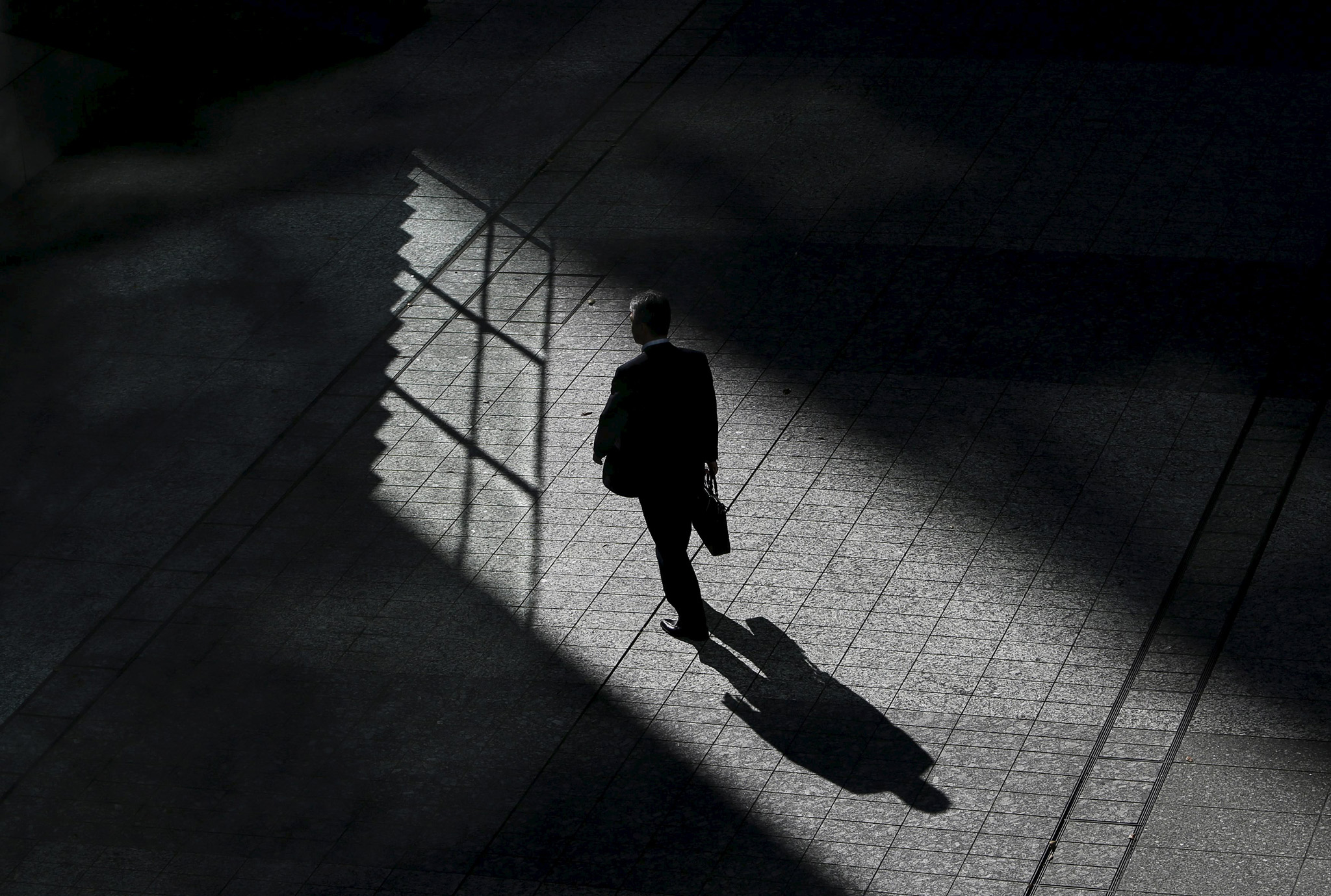 A man walks on a street between buildings at a business district in Tokyo
