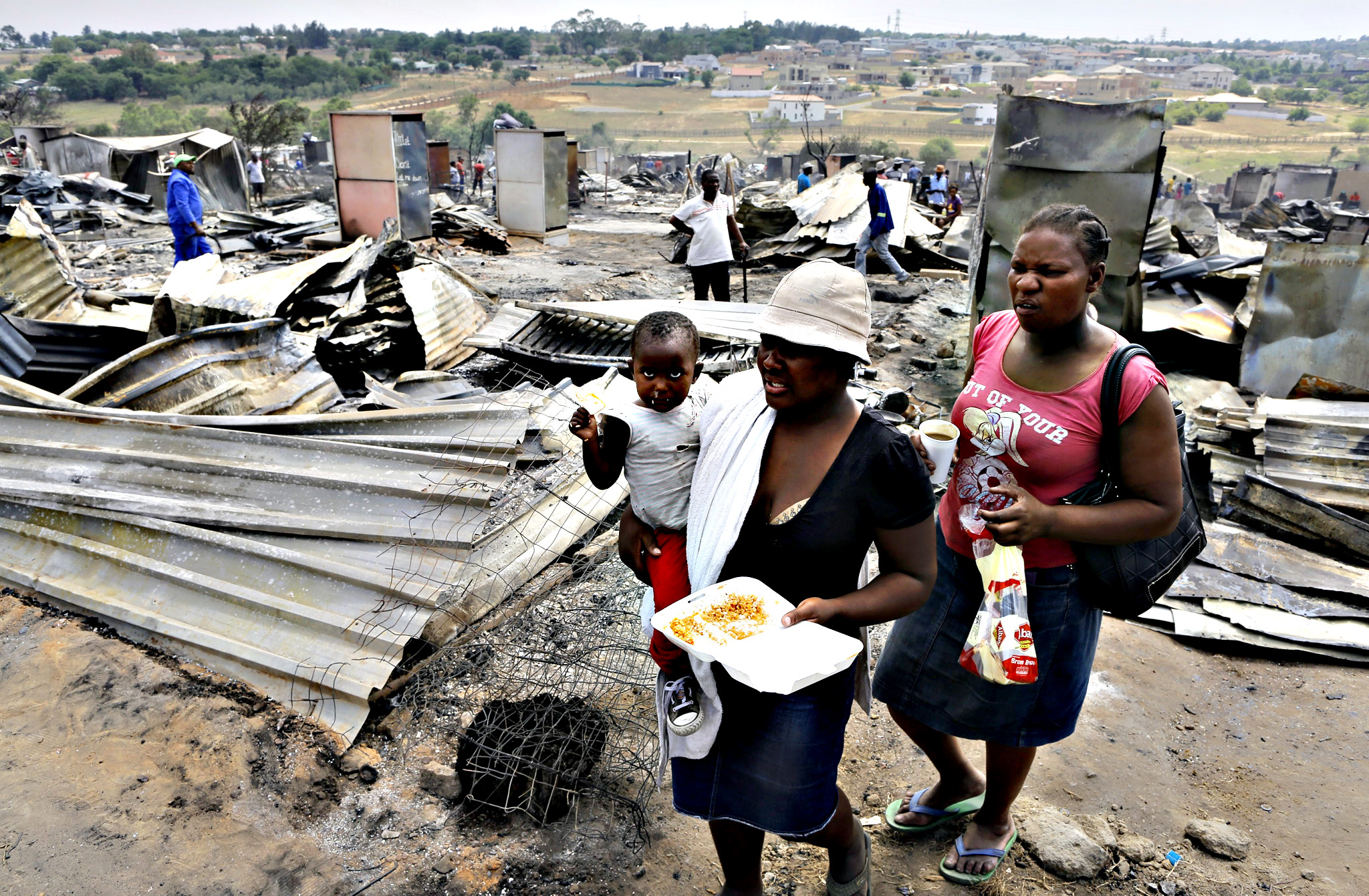 A mother carries her son through burnt out shacks after they where raised to the ground in a fire that destroyed 250 homes at the informal settlement in Kaya Sands, Johannesburg on Thursday. The fire yesterday fueled by high winds and a heat waves swept through the shacks of the settlement. No one was killed in the fire but hundreds of families have been left homeless.