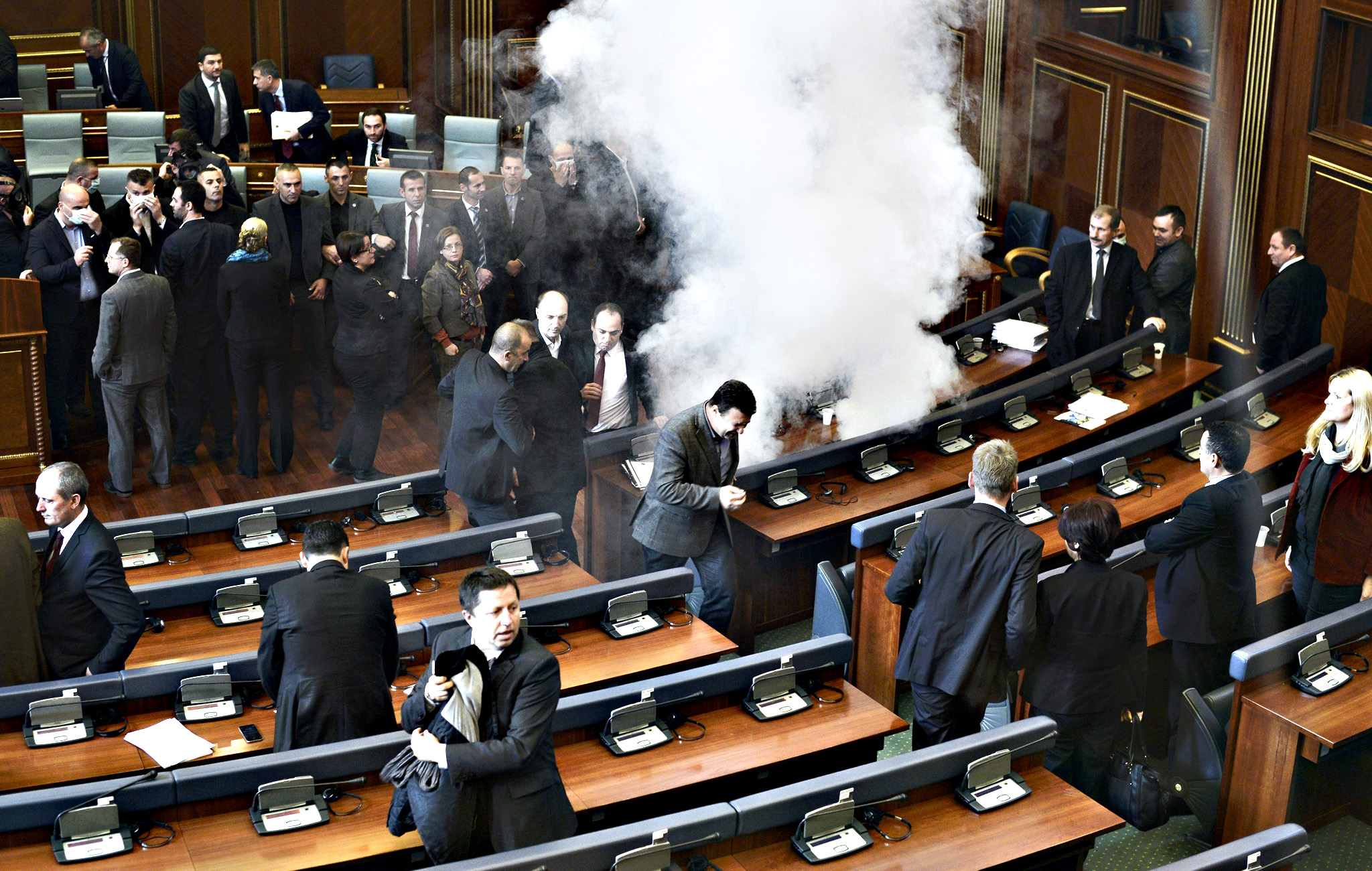 Opposition lawmakers throw tear gas during a session of Kosovo's parliament in Pristina, Kosovo, on Monday. Opposition lawmakers used tear gas at the start of the parliament session to protest against the agreements that Kosovo's government reached during the EU-brokered dialogue with Serbia.