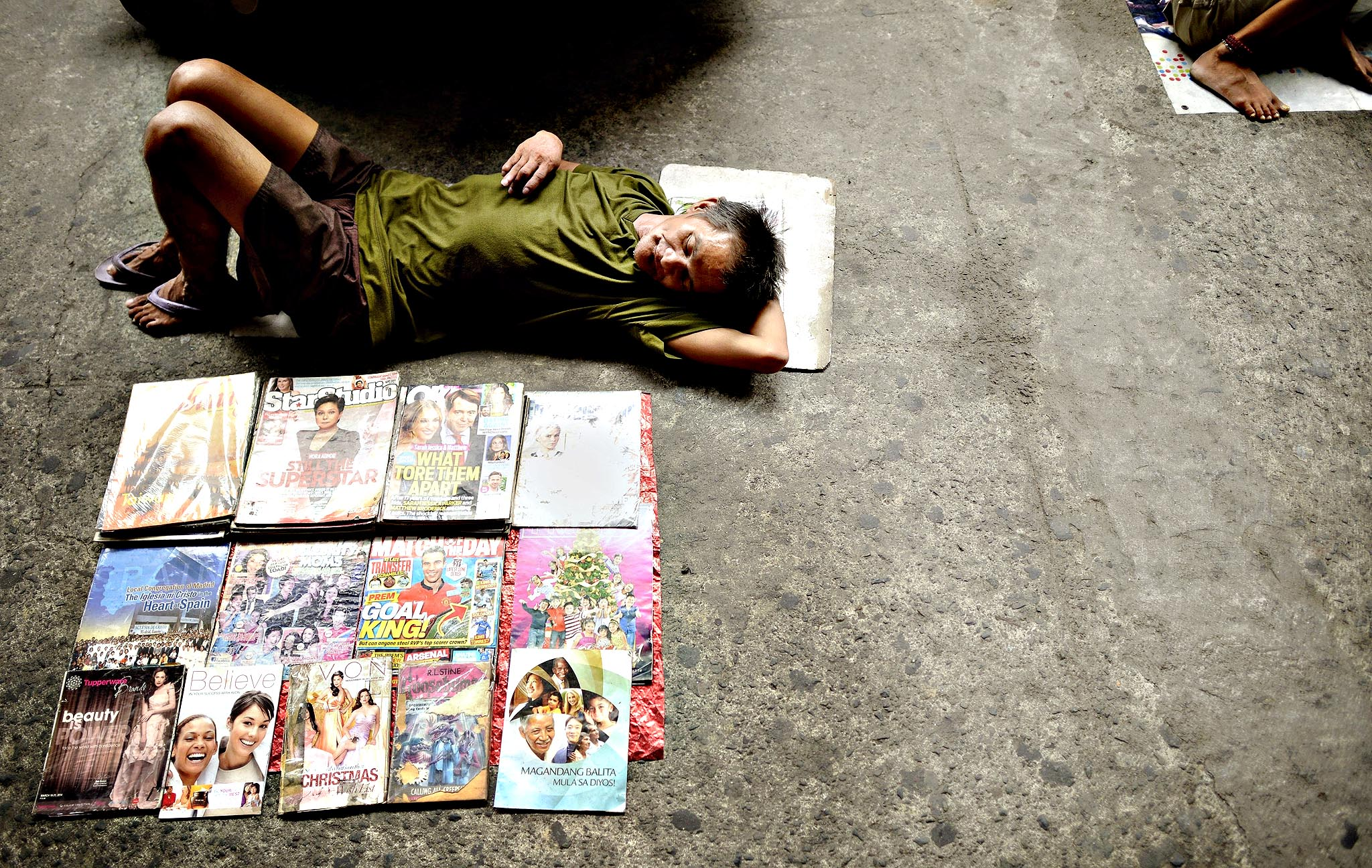 A vendor of used magazines sleeps along a street in Manila on Monday
