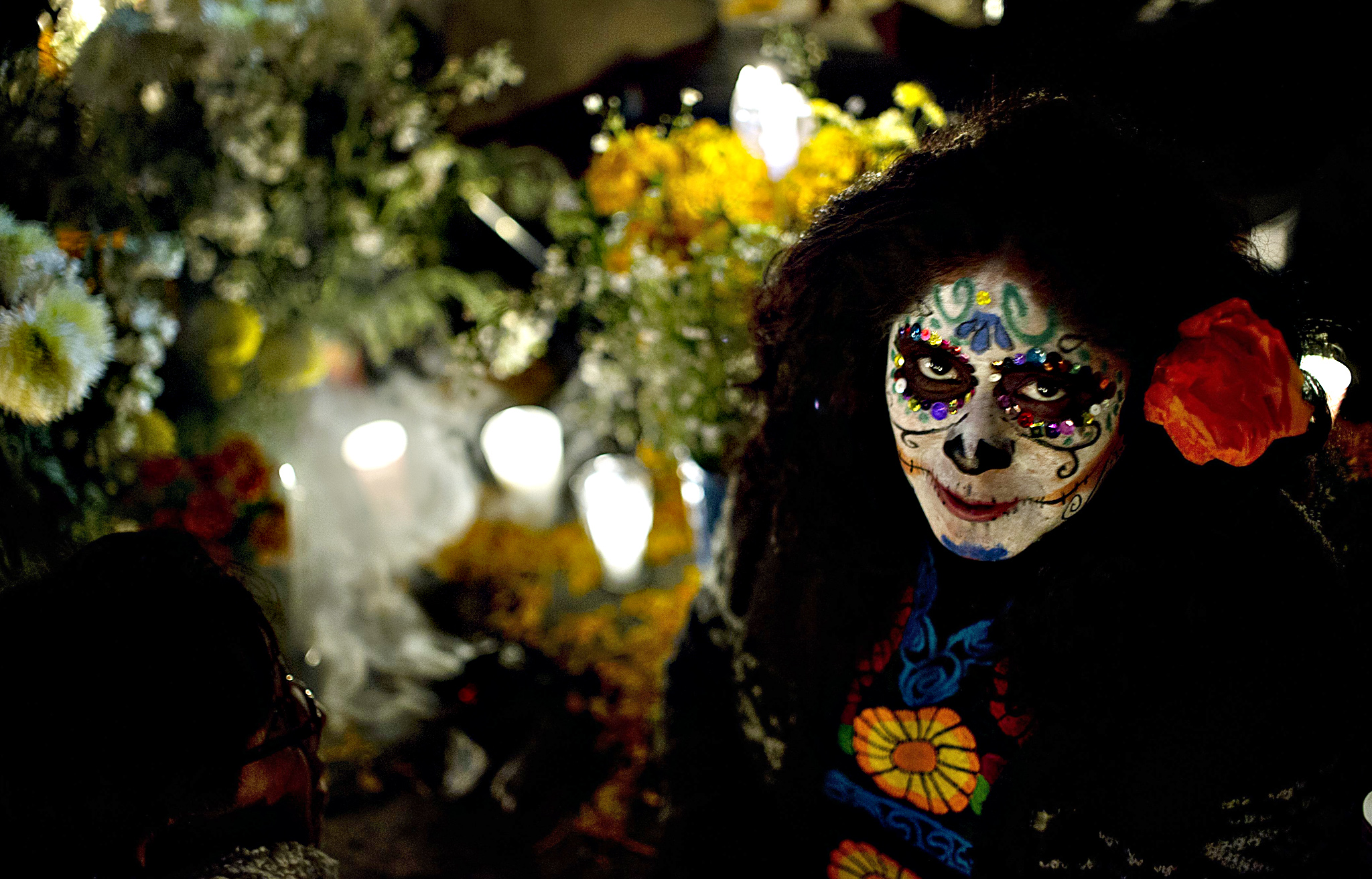 Residents of Mixquic town visit a local cemetery to place flowers, food, candles and balloons at the tombs of their beloved during the celebration of All Souls Day in Mixquic, Mexico