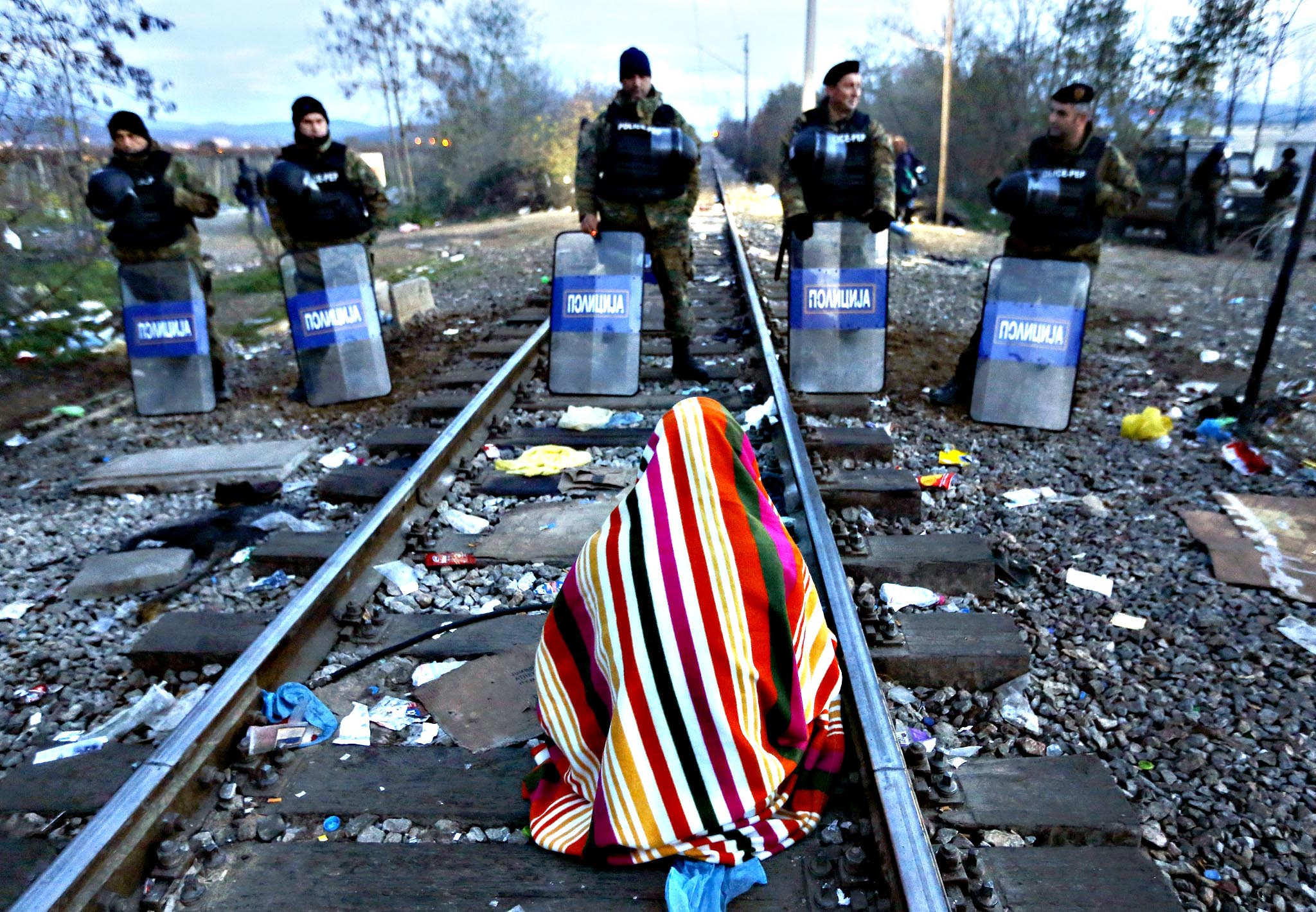 Stranded Iranian migrant Hamid, 34, an electrical engineer from the Iranian town of Sanandij sits on rail tucks in front of Macedonian riot police guarding the borderline between Greece and Macedonia near the Greek village of Idomeni November 23, 2015. Hamid and a dozen other Iranian migrants are on hunger-strike for a second day. Balkan countries have begun filtering the flow of migrants to Europe, granting passage to those fleeing conflict in the Middle East and Afghanistan but turning back others from Africa and Asia