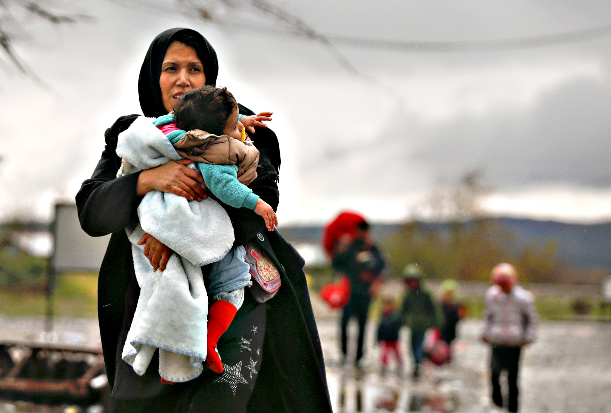 "A migrant carries her child after crossing the border from Greece into Macedonia, near Gevgelija, Macedonia on Friday. Macedonia, Serbia and other Balkan states have implemented a new policy to filter the flow by granting passage onwards toward Western Europe only to those fleeing conflicts in Syria, Iraq and Afghanistan, who are seen as genuine asylum seekers rather than ""economic migrants."""