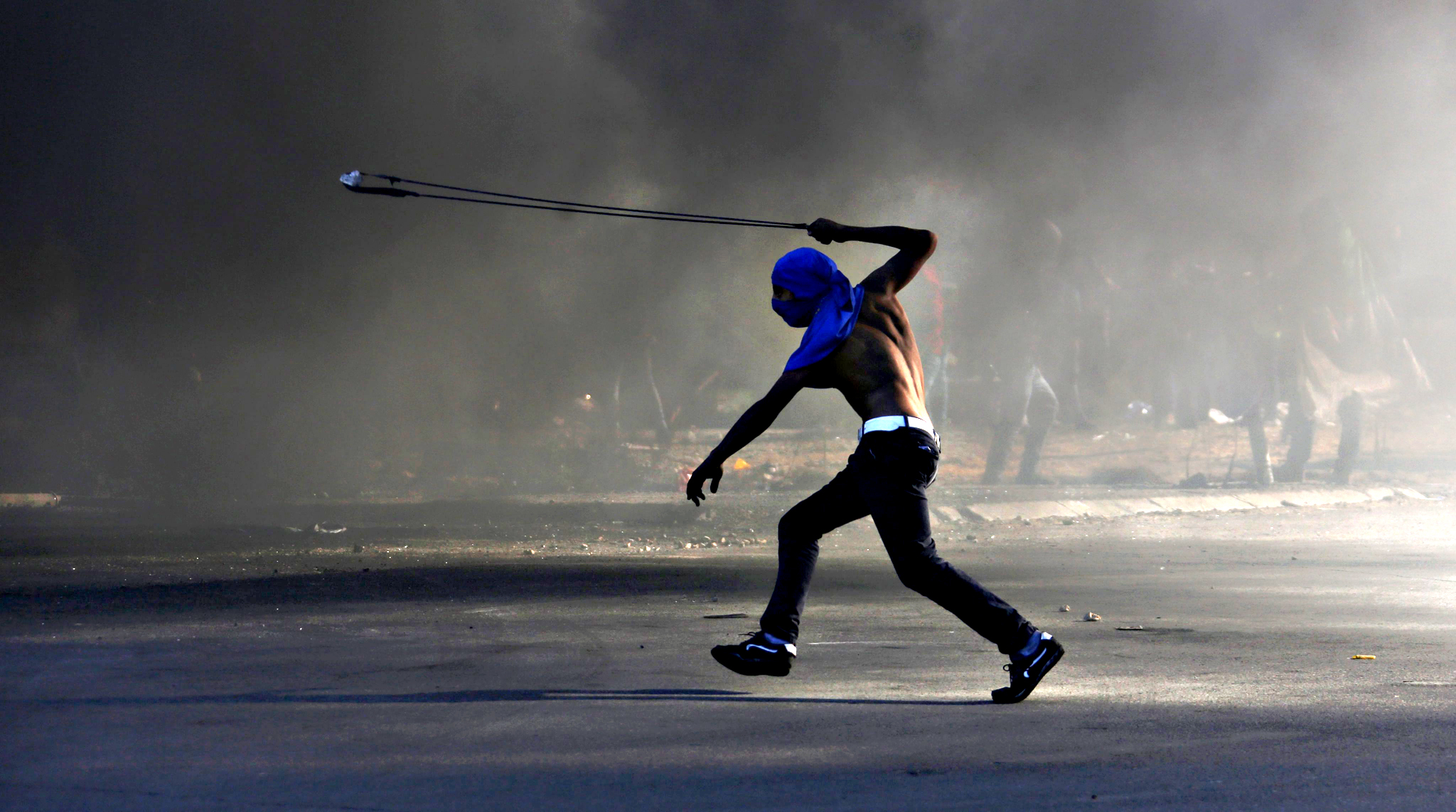 A Palestinian protester hurls stones at Israeli soldiers during clashes in Beit El, on the outskirts of the West Bank city of Ramallah, on Friday. According to reports, 22 Palestinians were injured during the clashes.