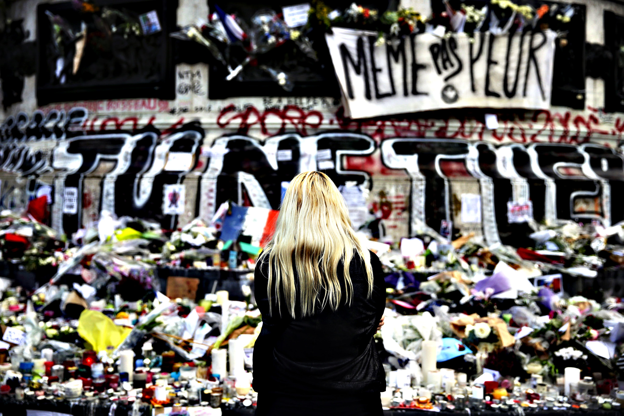 A woman stands in front of a makeshift memorial made up with flowers, candles and messages, on November 17, 2015, at the Place de la Republique square in Paris, in tribute to victims of the attacks claimed by Islamic State which killed at least 129 people and left more than 350 injured on November 13 in Paris.