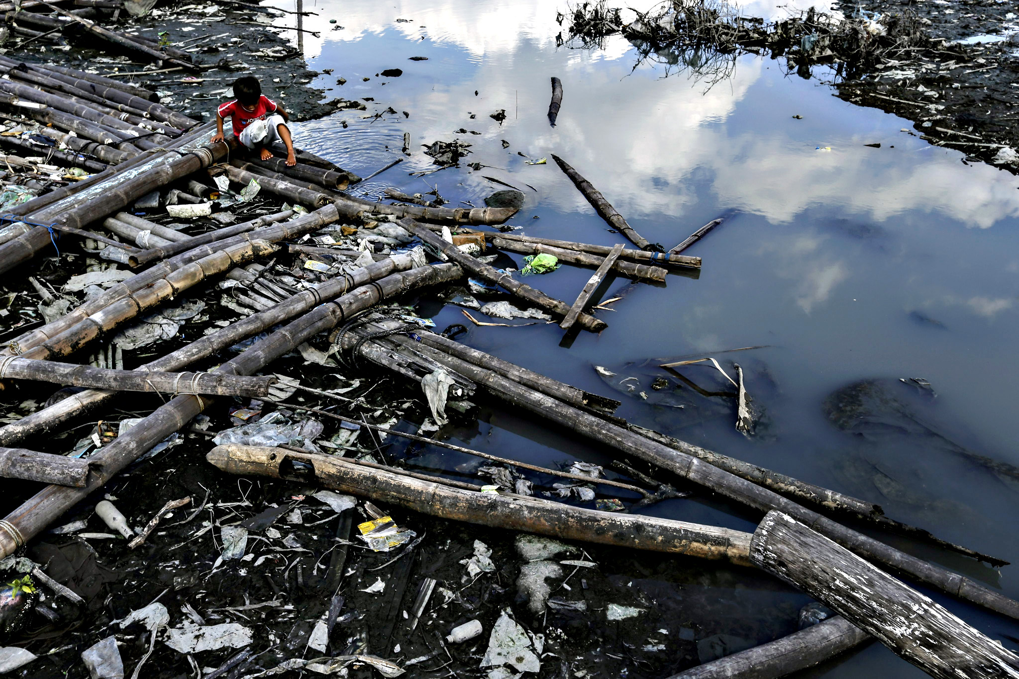 A Filipino informal settler boy frolics at a polluted coastline at a fishing village in Paranaque city, south of Manila, Philippines, on Friday. Street vendors and homeless people near the APEC 2015 venues have been rounded up, while protesters were told that they demonstrate only in designated areas away from the site of the summit.