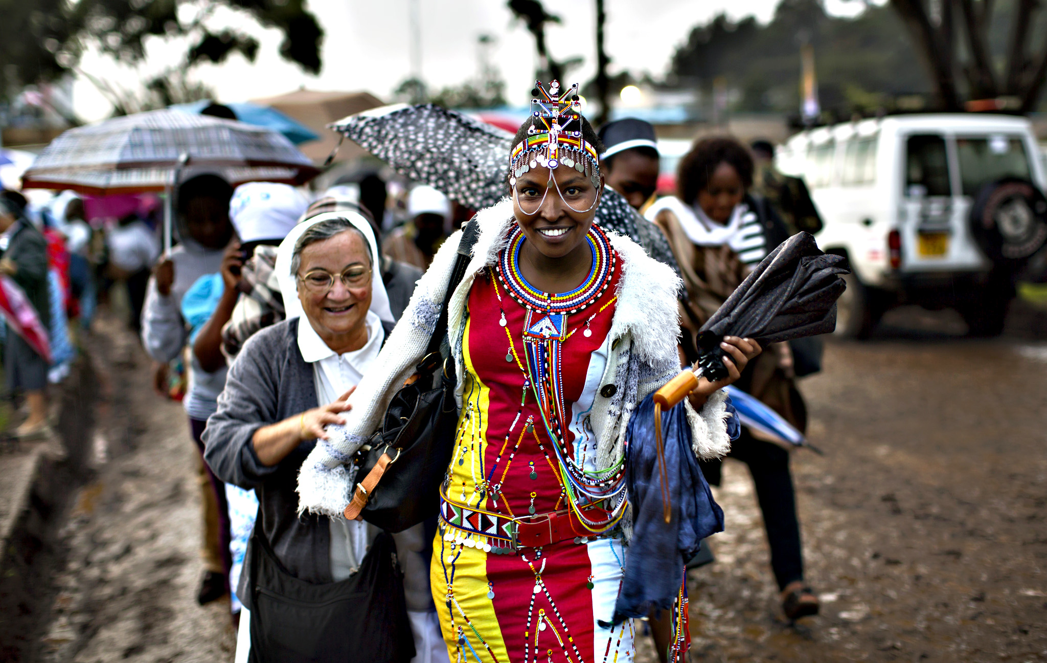 A Catholic sister and a Maasai woman arrive just after dawn in the rain and mud to attend a Mass to be given by Pope Francis at the campus of the University of Nairobi in Kenya Thursday, Nov. 26, 2015. Pope Francis is in Kenya on his first-ever trip to Africa, a six-day pilgrimage that will also take him to Uganda and the Central African Republic.