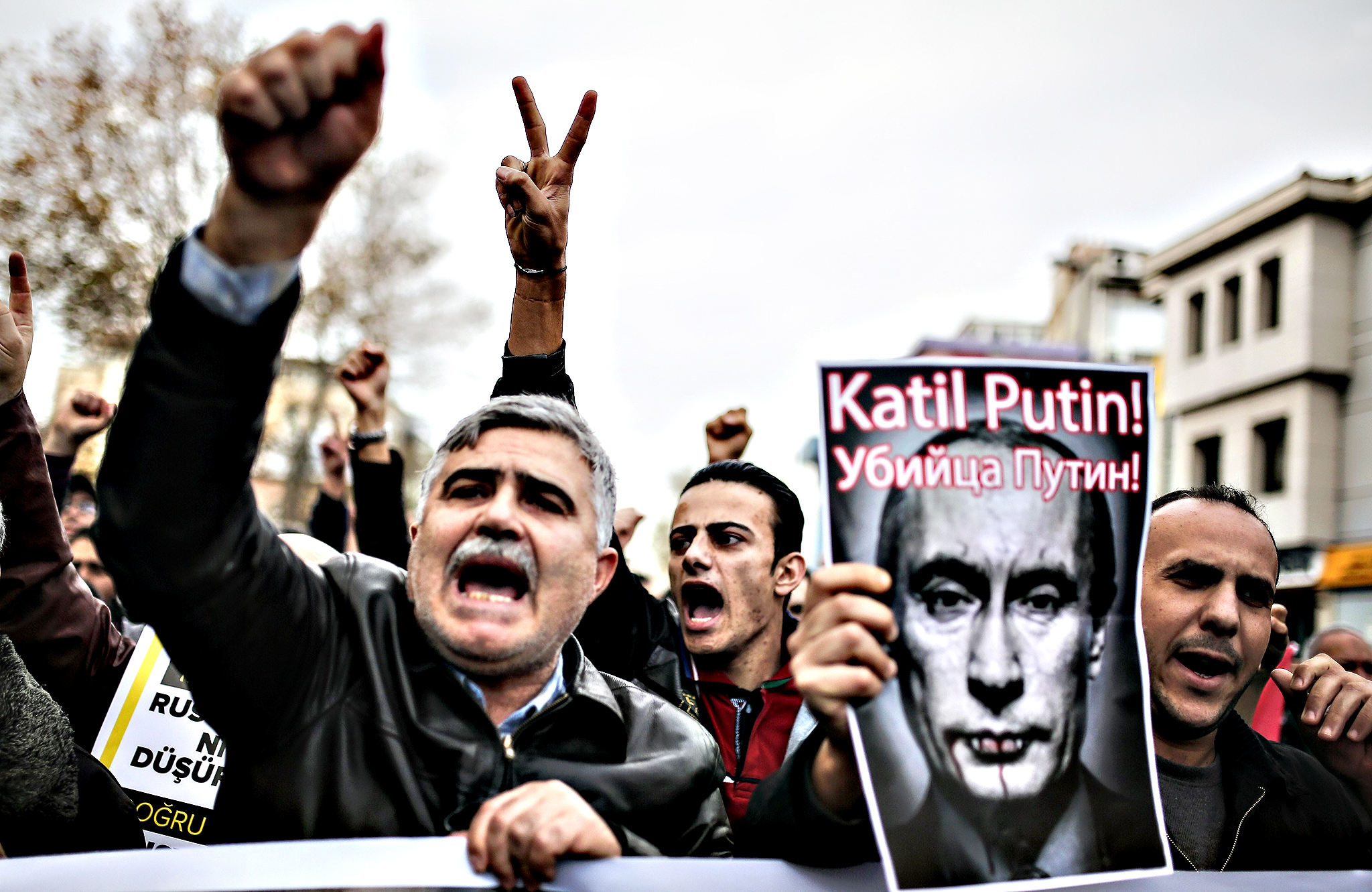 "Protesters shout slogans and hold a poster depicting Russian President Vladimir Putin and reading ""Putin, killer!"" during a demonstration against Russia on November 27, 2015, in Fatih district in Istanbul. Russia's Foreign Minister Sergei Lavrov on November 27 said that Ankara has crossed the line by shooting down a Russian warplane this week and warned the incident could severely undermine Turkey's interests"