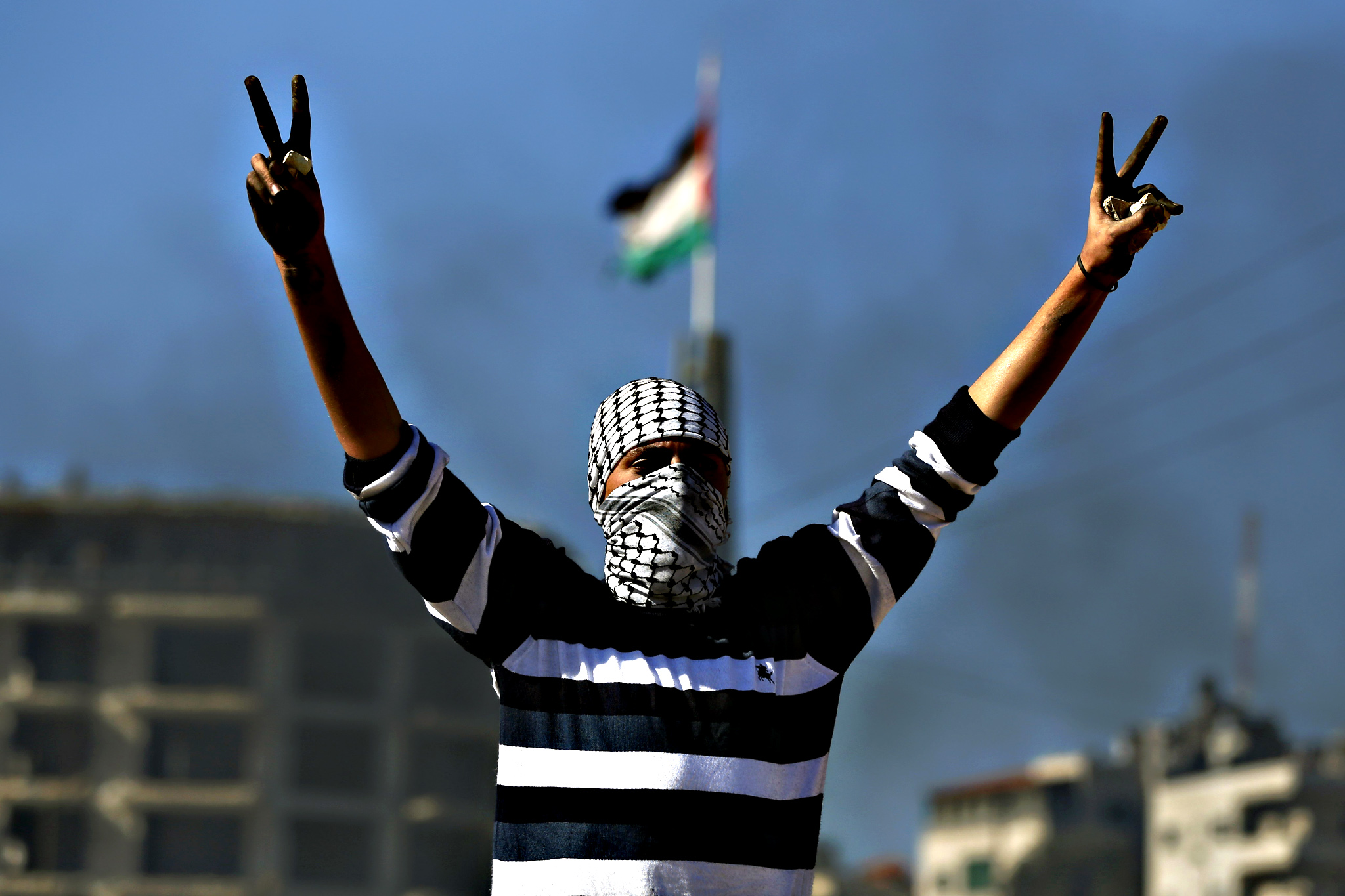 "A masked Palestinian demonstrator flashes the ""V"" for victory sign during clashes with Israeli security forces in the Palestinian town of al-Bireh on the outskirts of Ramallah in the Israeli-occupied West Bank, on Tuesday"