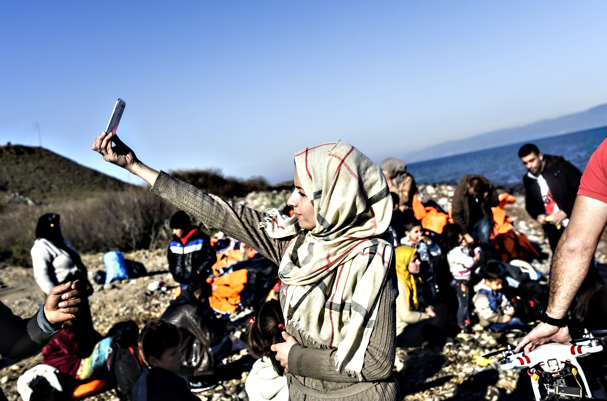 A woman takes a selfie after arriving, along with other migrants and refugees, on the Greek island of Lesbos by crossing the Aegean Sea from Turkey on November 13, 2015. EU leaders on November 12 struck an aid-for-cooperation deal with Africa and proposed a summit this year with Turkey in a two-front push with wary partners to tackle an unprecedented migrant crisis