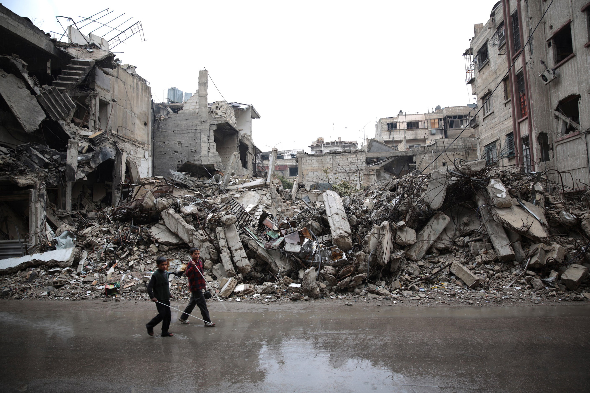 Syrian children walk past the rubble of destroyed buildings in the rebel-held area of Douma, east of the Syrian capital Damascus