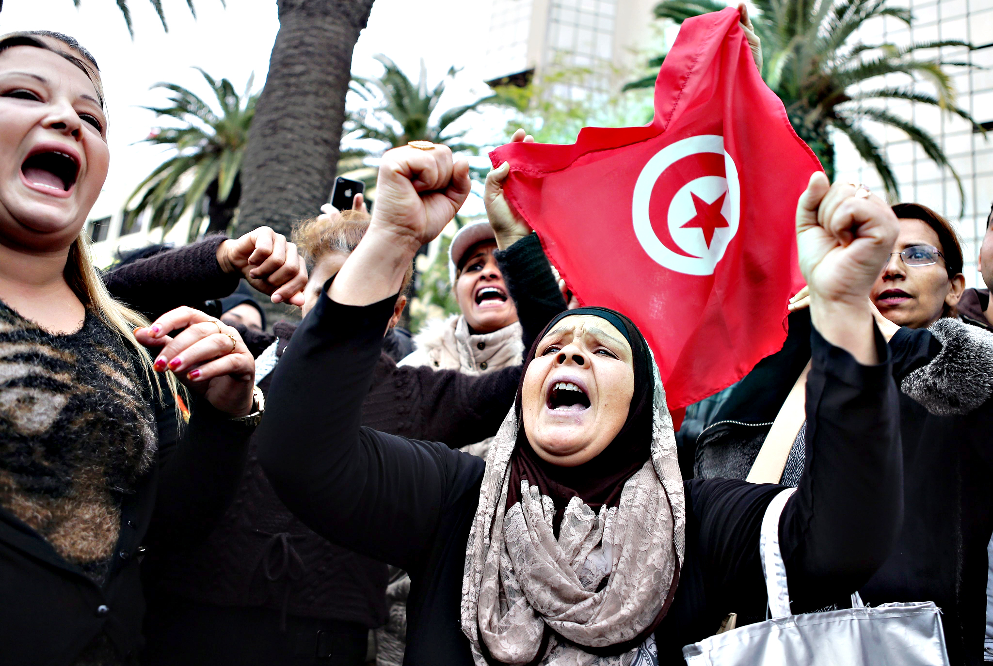 Tunisians shout slogans and hold Tunisian flags during a demonstration in solidarity with victims of a bomb attack on a bus transporting Tunisian presidential guards a day earlier, in Tunis, Tunisia, on Wednesday. Tunisian Prime Minister Habib Essid warned that his government would strictly enforce a curfew and anti-terrorism measures after 12 presidential guards were killed in a bombing on 24 November. Investigators were examining a 13th corpse to determine whether it was that of a civilian victim or a suicide attacker. Officials have said they suspect the blast was a suicide bombing.