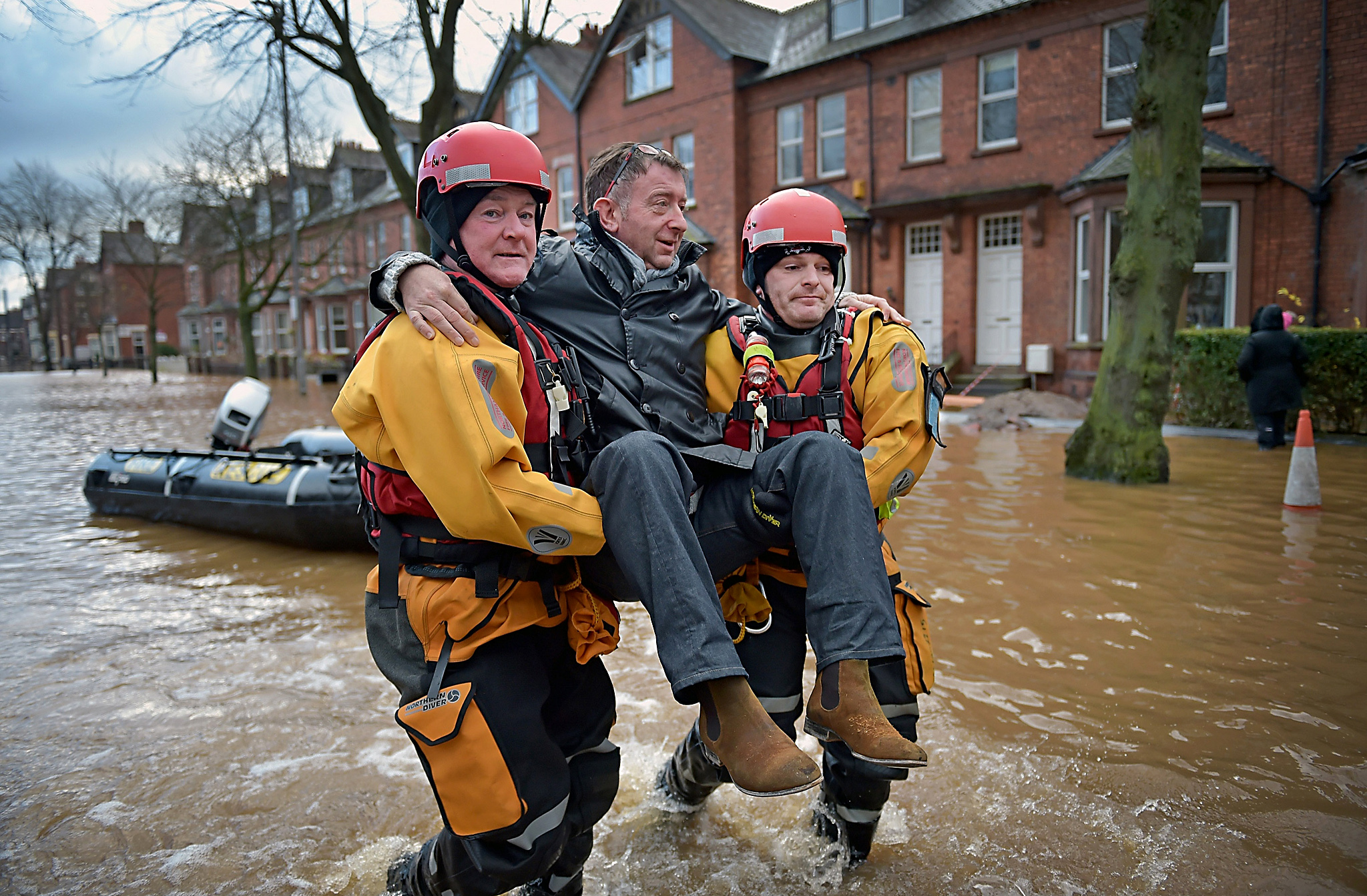 Flooding Chaos As Thousands Evacuated Across Northern England...CARLISLE, ENGLAND - DECEMBER 07:  Rescue teams carry people to safety through the flood water as they continue to to evacuate homes after Storm Desmond caused flooding on December 7, 2015 in Carlisle, England. Storm Desmond has brought severe disruption to areas of northern England with dozens of flood warnings remaining in place throughout the country. (Photo by Jeff J Mitchell/Getty Images)