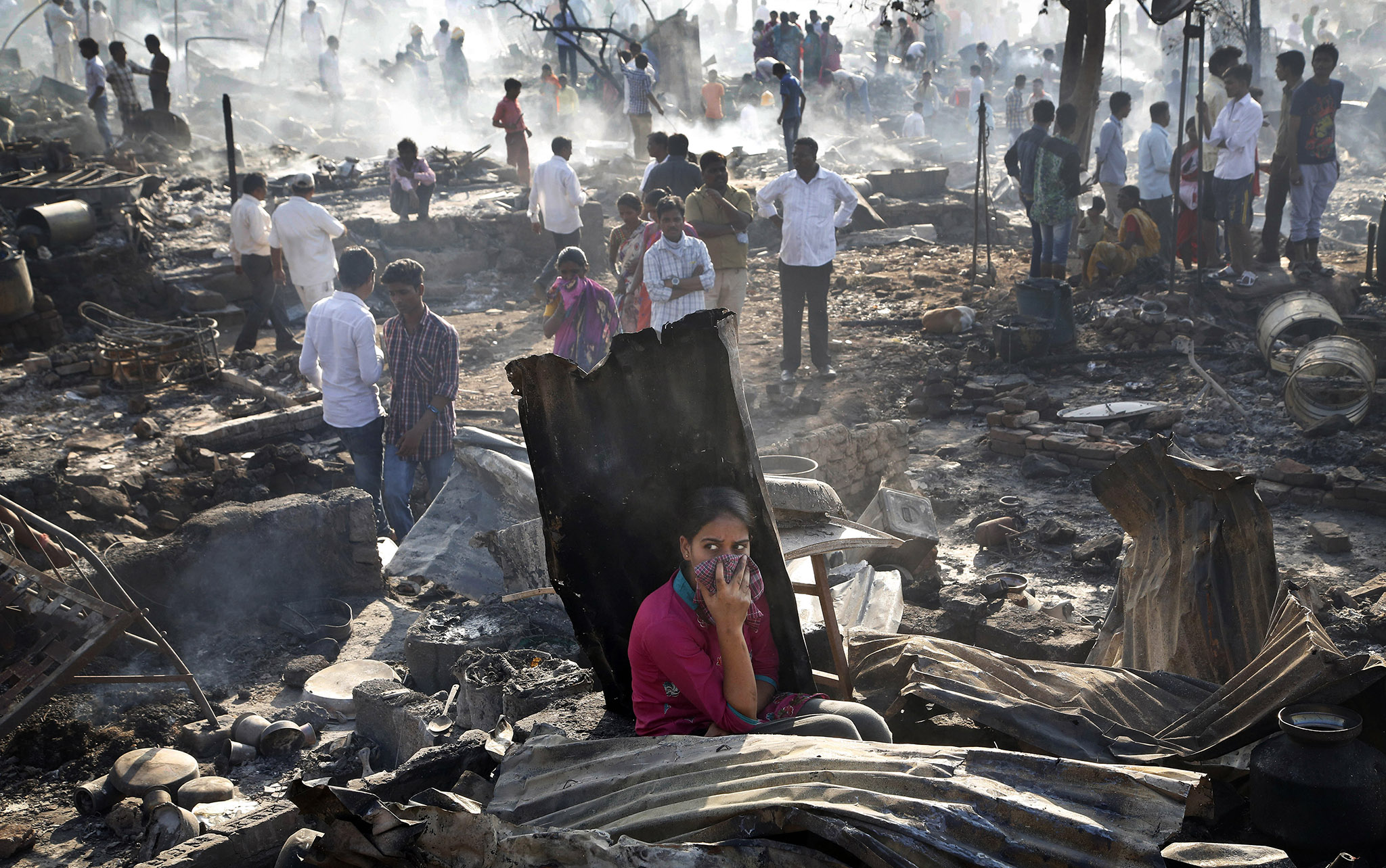 People look at the devastation caused by fire that broke out at slums in Kadivali area of Mumbai, India. Hundreds of homes were reportedly destroyed as fire tenders laboured to reach the source in the heavily congested area.