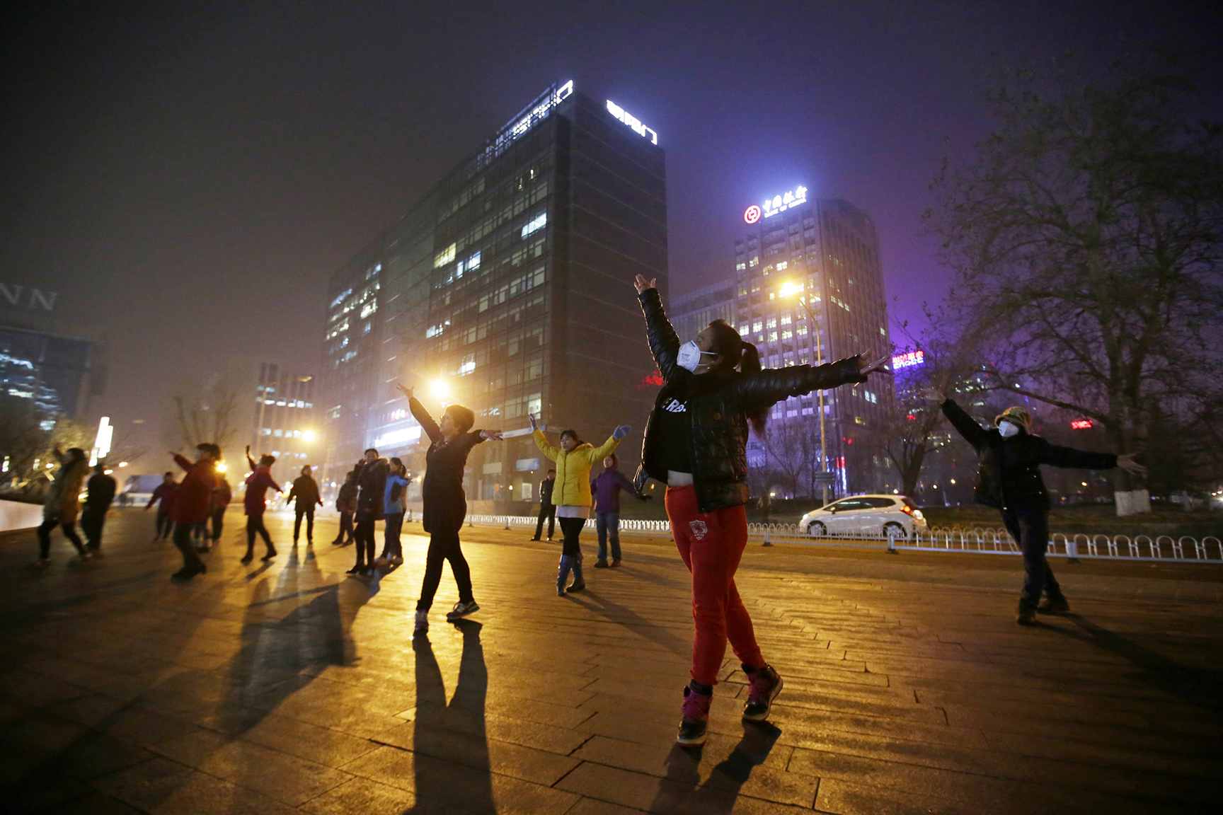 Women wearing masks and other residents dance during their daily exercise amid the heavy smog in Beijing