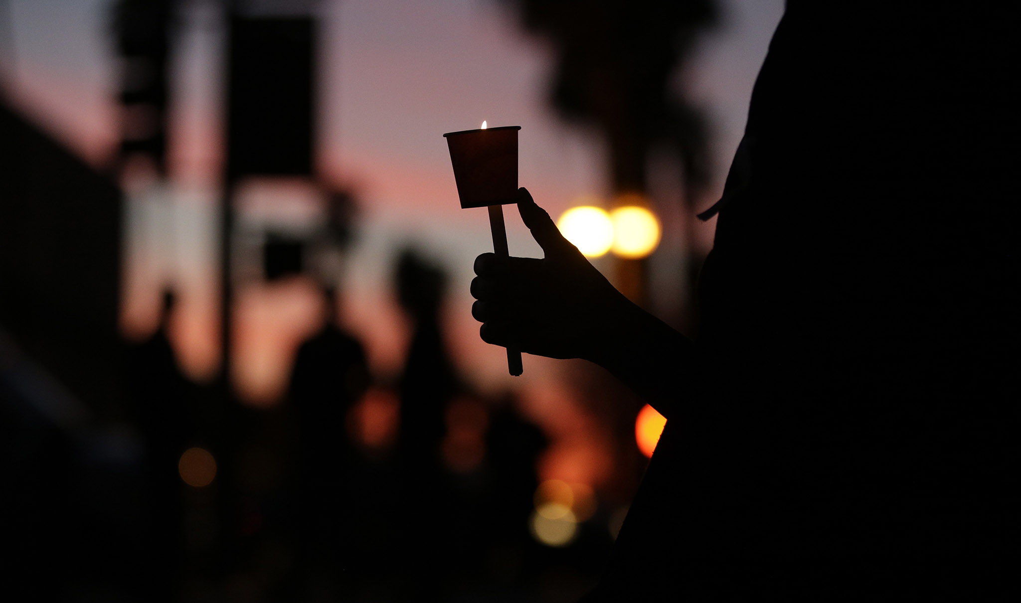 Cathleen Garcia holds a candle during a vigil to honour shooting victims in San Bernardino, California