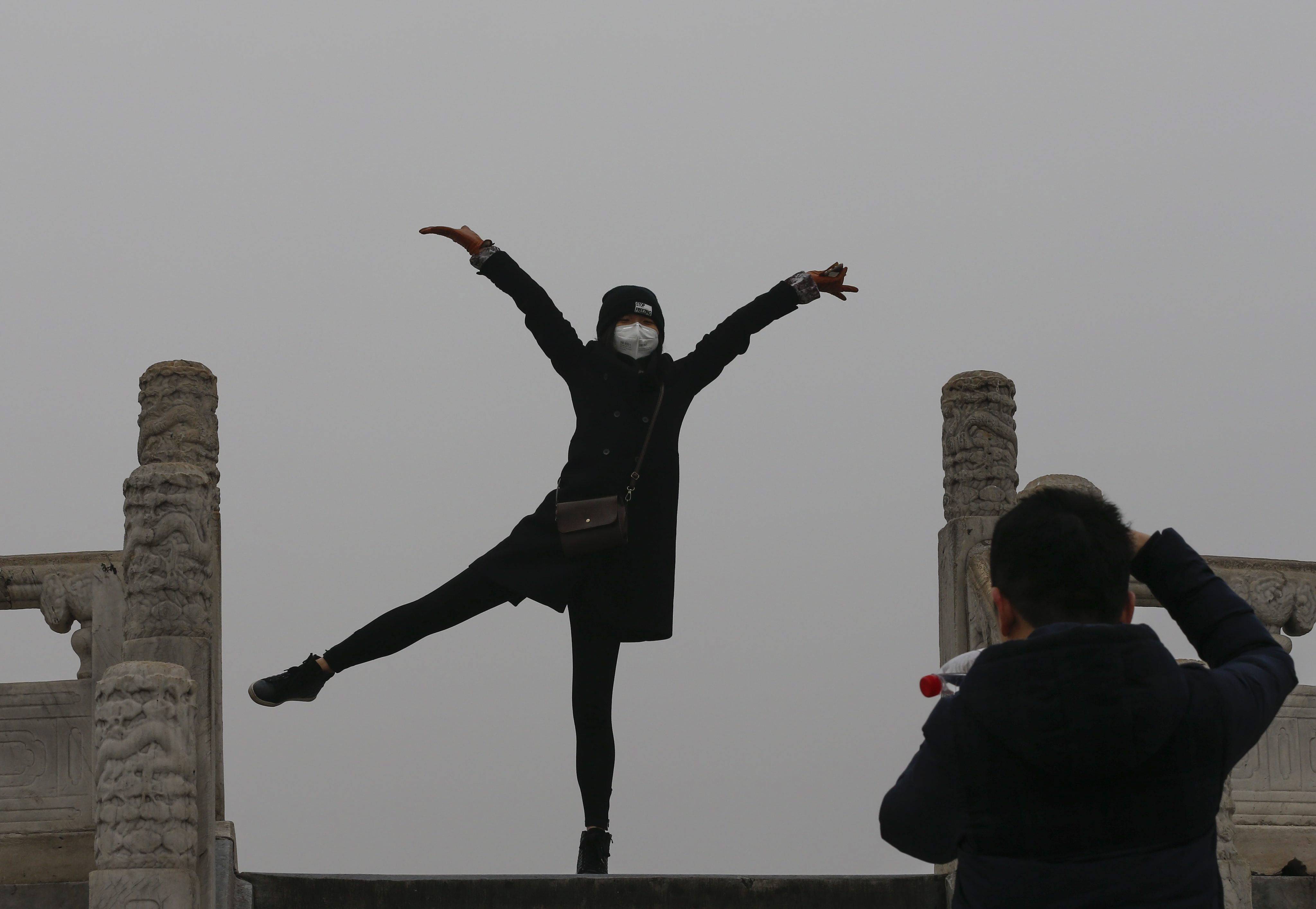 A woman wearing a protective mask against smog poses for photos at the Temple of Heaven Park in Beijing, China