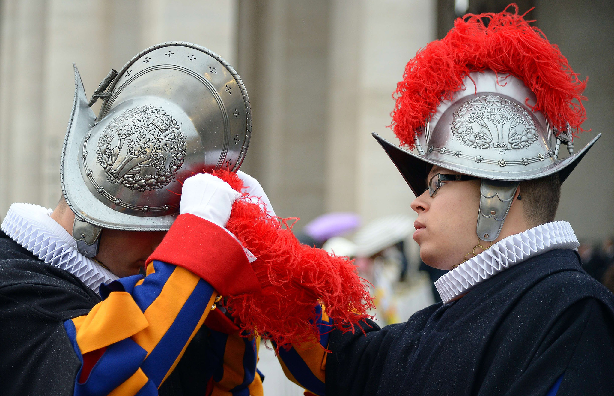 A Swiss guard helps a collegue to adjust his helmet at St Peter's square before the start of the Jubilee Year of Mercy in the Vatican.