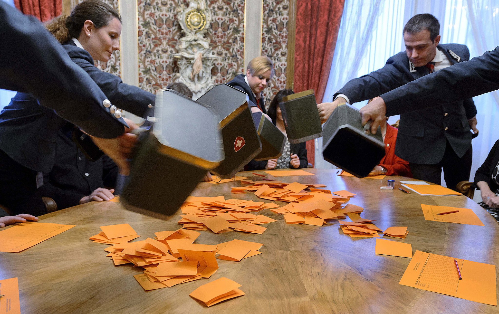 Ushers empty ballot boxes during an election meeting of the Swiss Federal assembly at the House of Parliament in Bern. Swiss lawmakers are due to elect a new federal government, with the populist right-wing, anti-immigrant Swiss People's Party expected to secure a second post after triumphing in the parliamentary polls