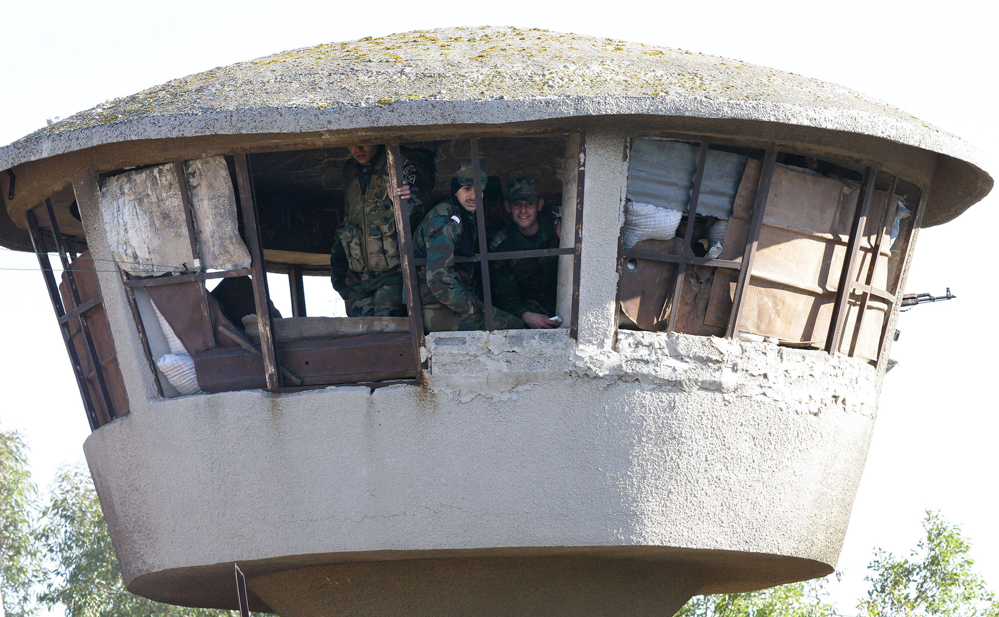 Members of the Syrian government forces sit in a tower at a military base as hundreds of civilians and Syrian rebel forces began evacuating the last opposition-held district of Waer in the central city of Homs