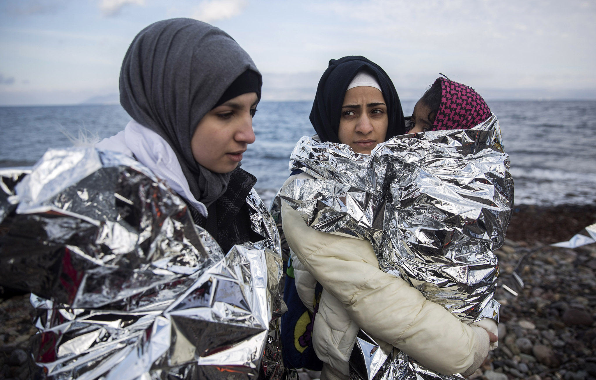 Women covered with thermal blankets after their arrival with other migrants and refugees on a dinghy from the Turkish coast to the northeastern Greek island of Lesbos.