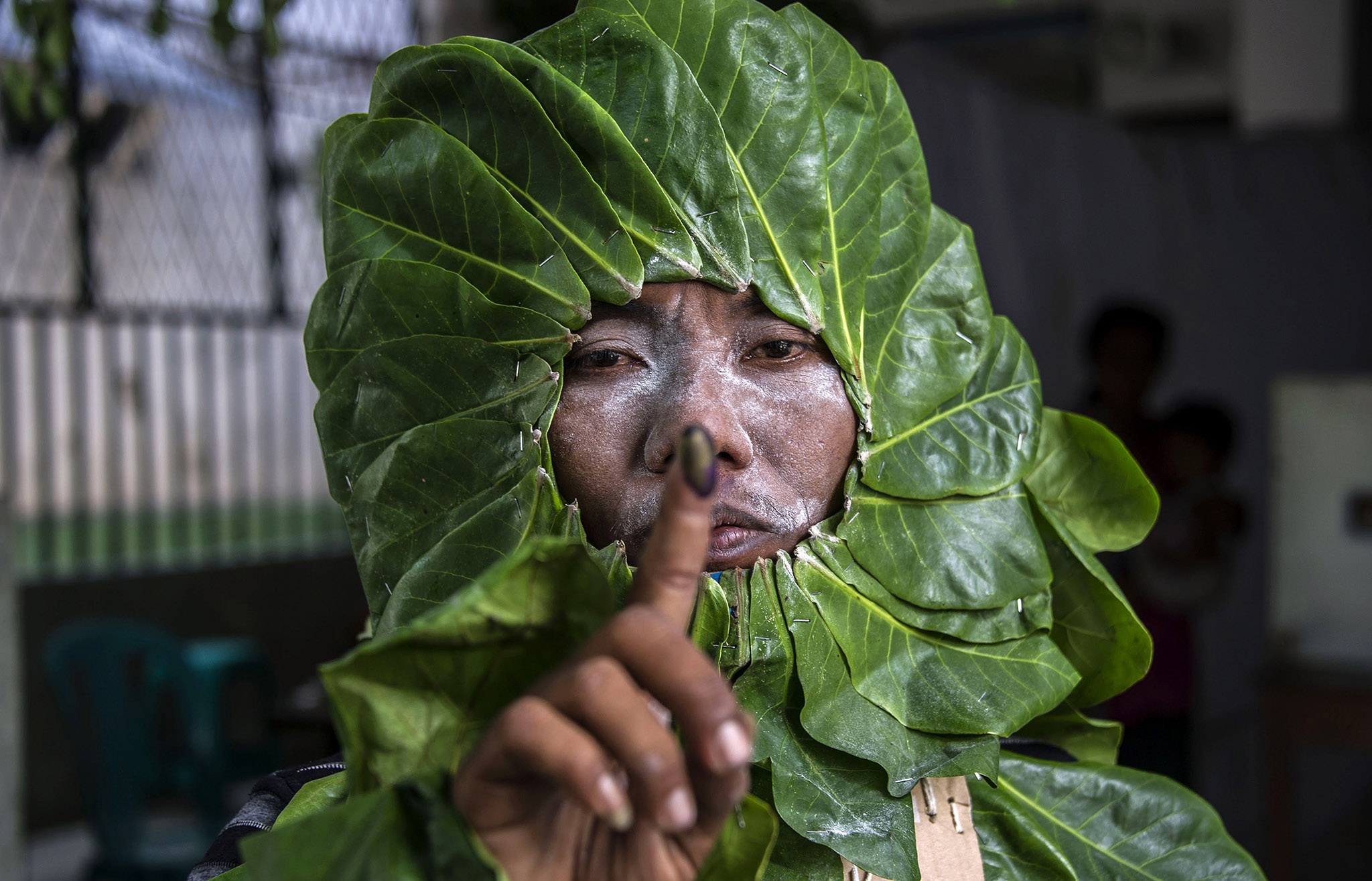 An Indonesian man dressed as a plant to increase peoples' awareness of the environment shows his inked finger after voting in the country's first nationwide regional elections, in Surabaya