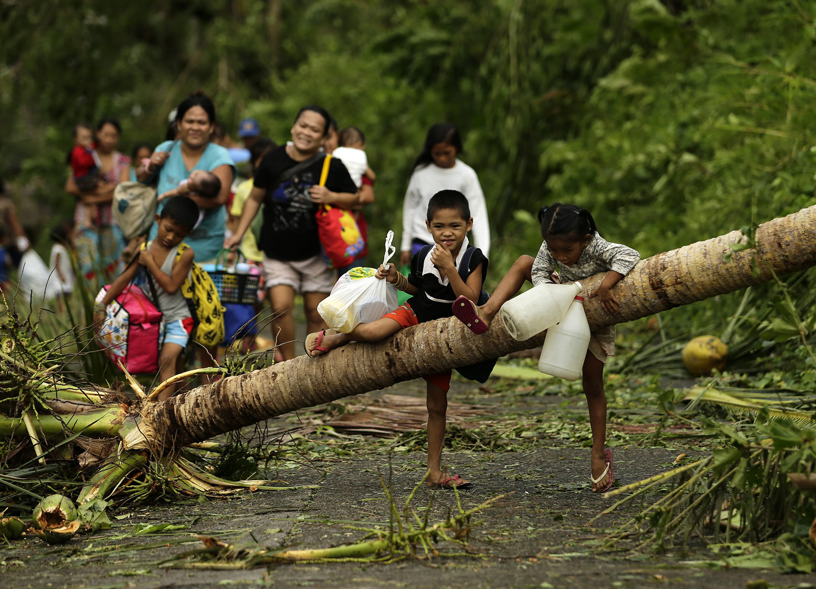 Filipino evacuees walk on a path with debris in the typhoon-hit town of Juban, Sorsogon province, southern Philippines, 15 December 2015. Typhoon Melor weakened slightly as it barreled through the Philippine islands. causing power outages in towns and cities along its path and forcing thousands to flee their homes, officials said. It said 733,150 people had fled their homes amid threats of sea surges, flash floods and landslides.  EPA/FRANCIS R. MALASIG