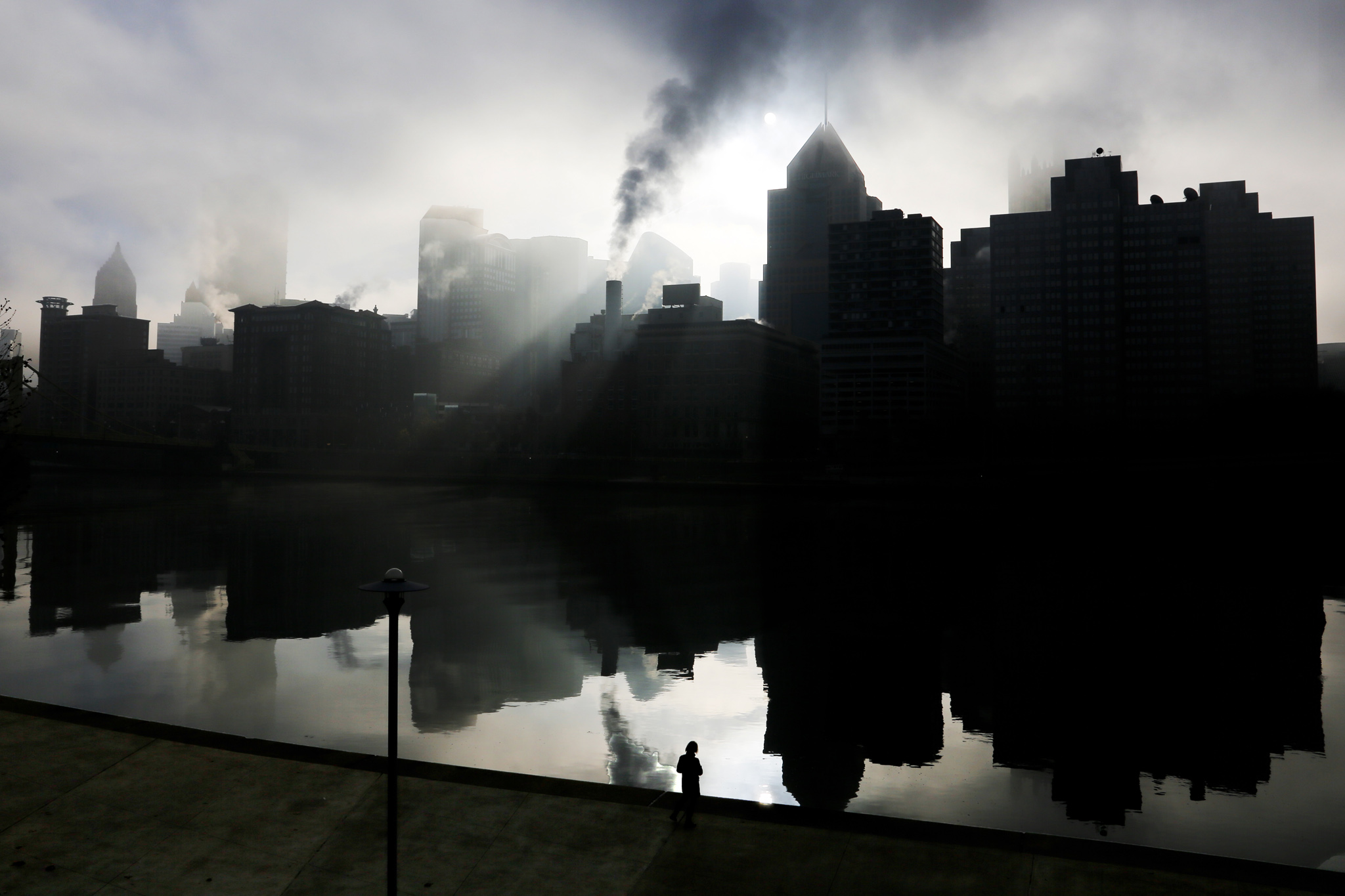 The skyline of downtown Pittsburgh is reflected in the Allegheny River as it is silhouetted by the sun rising on a foggy morning, Sunday, Dec. 6, 2015. (AP Photo/Gene J. Puskar)