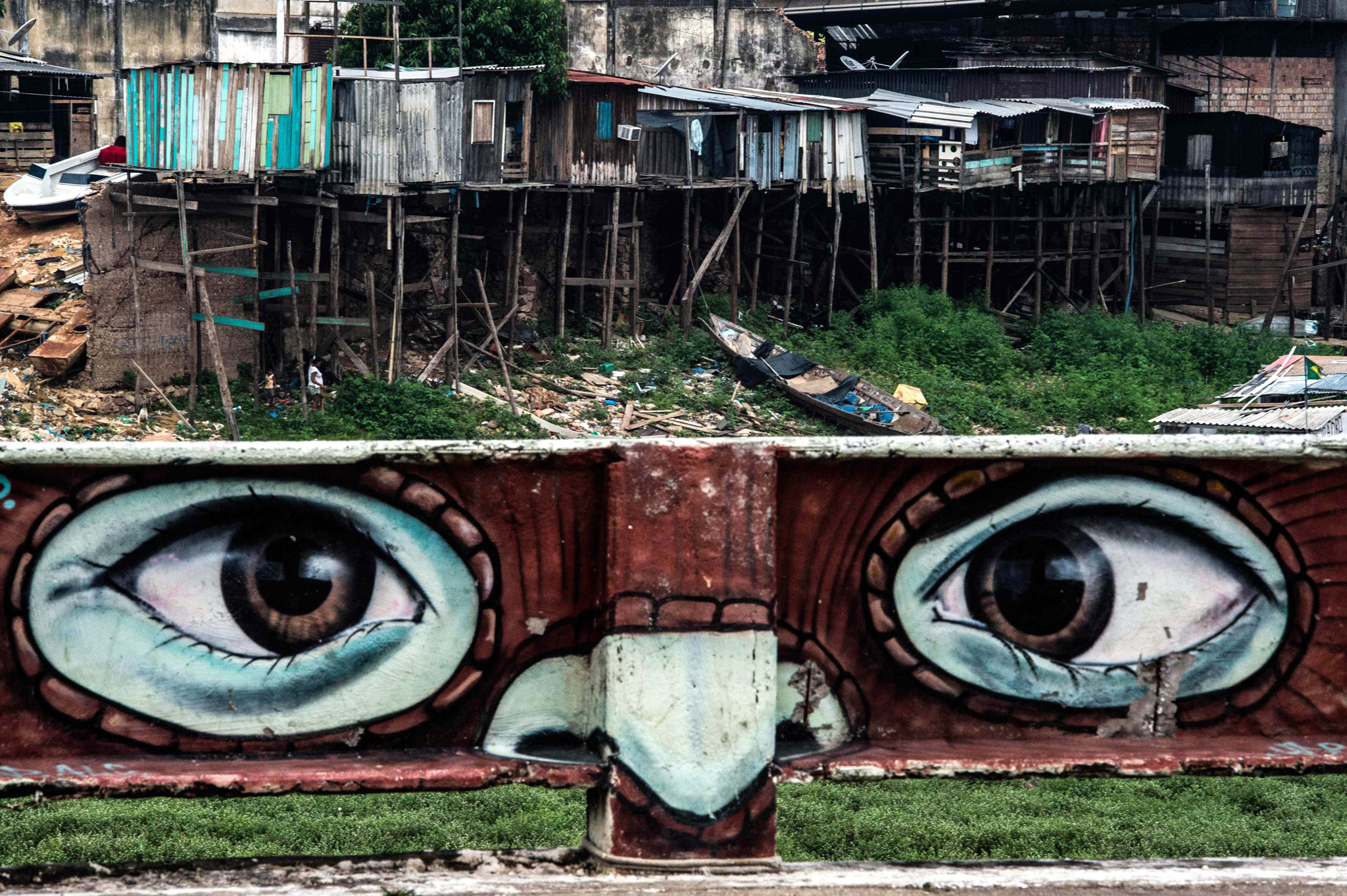 TOPSHOT - A mural is seen with a slum in...TOPSHOT - A mural is seen with a slum in the background on the bank of the Rio Negro (Black River), in Manaus, Amazonas state, Brazil on December 11, 2015.