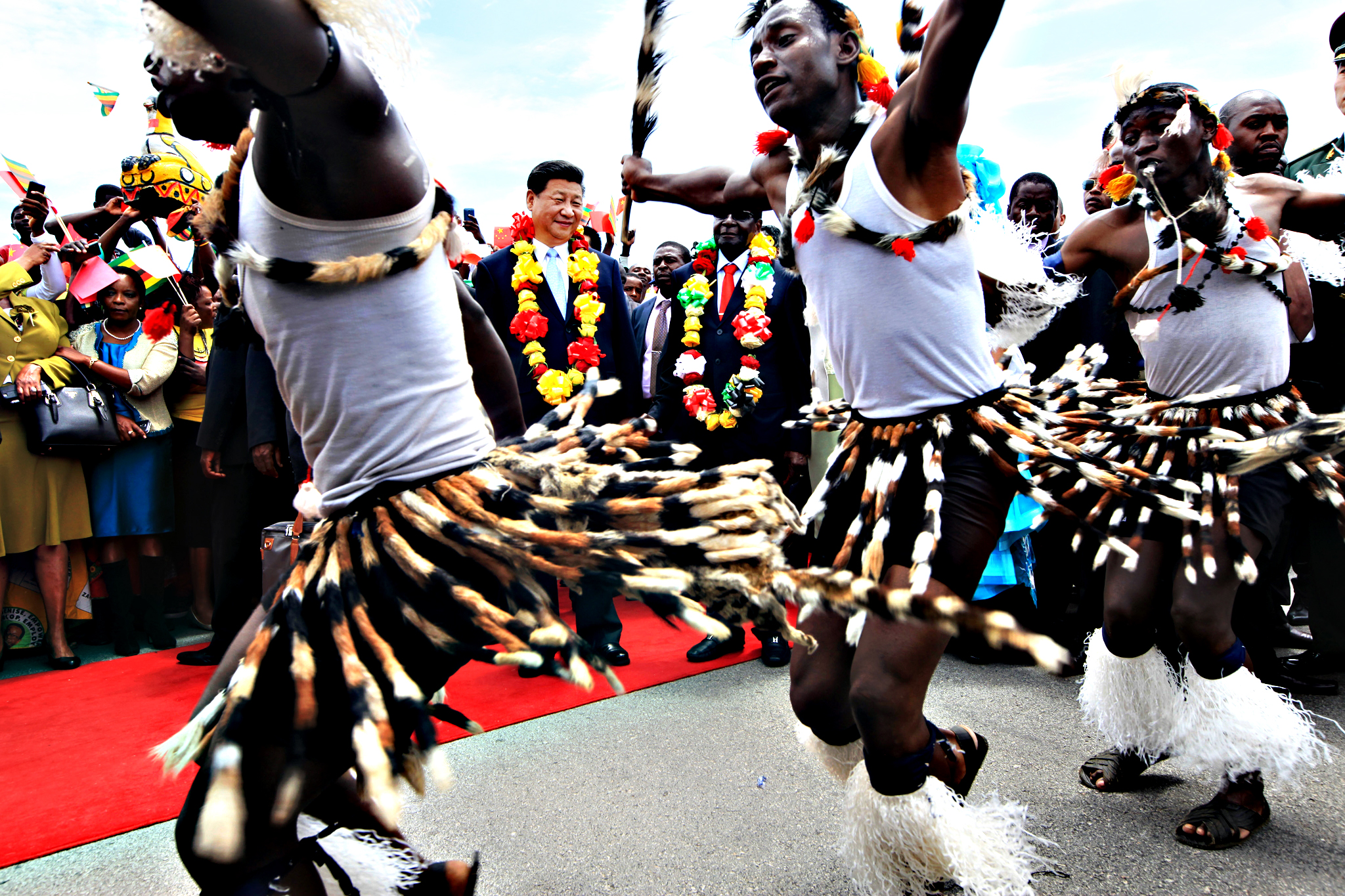 Chinese President Xi Jinping, centre, and Zimbabwean President Robert Mugabe, centre right,  watch a performance by Zimbabwean traditional dancers upon his arrival in Harare, Zimbabwe, Tuesday, Dec. 1. 2015. Jinping is in Zimbabwe for a two day State visit during which he is set to sign some bilateral agreements aimed at strengthening relationships between the two countries