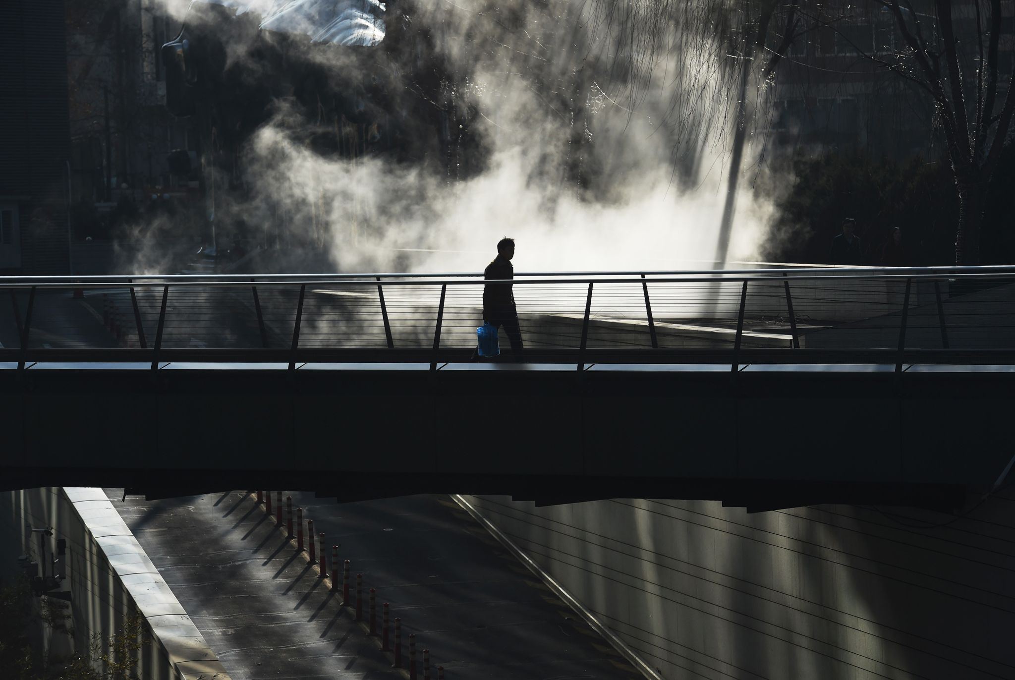 A man walks past steam rising from underground heating pipes outside a shopping mall in Beijing