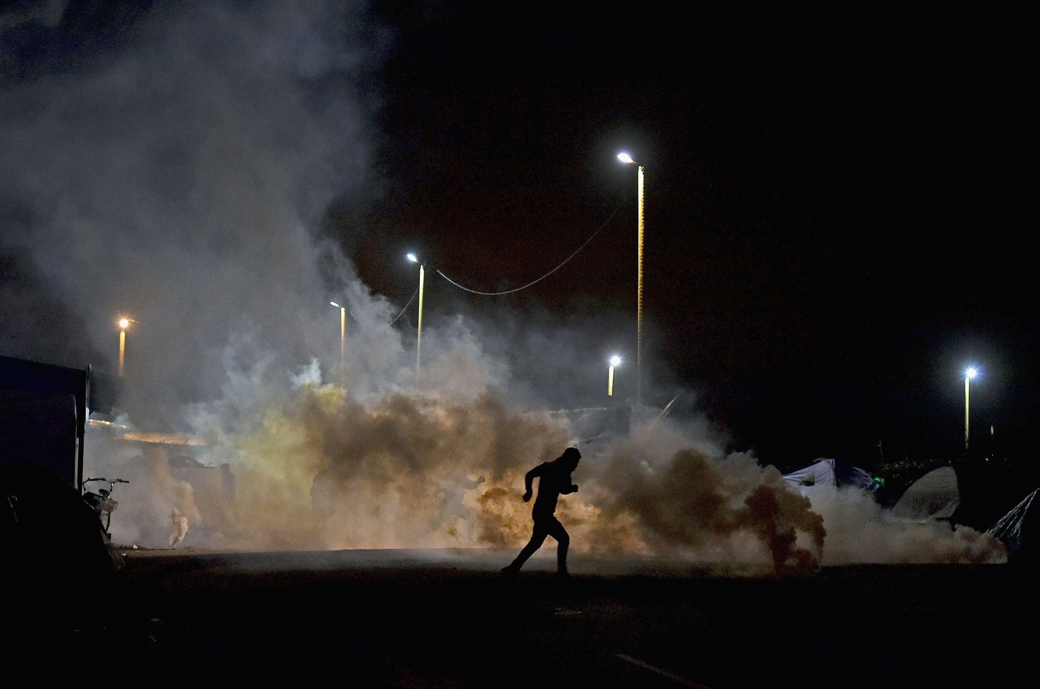 Migrants run as police fired tear gas into the entrance to the camp known as the 'New Jungle' on December 2, 2015 in Calais, France.