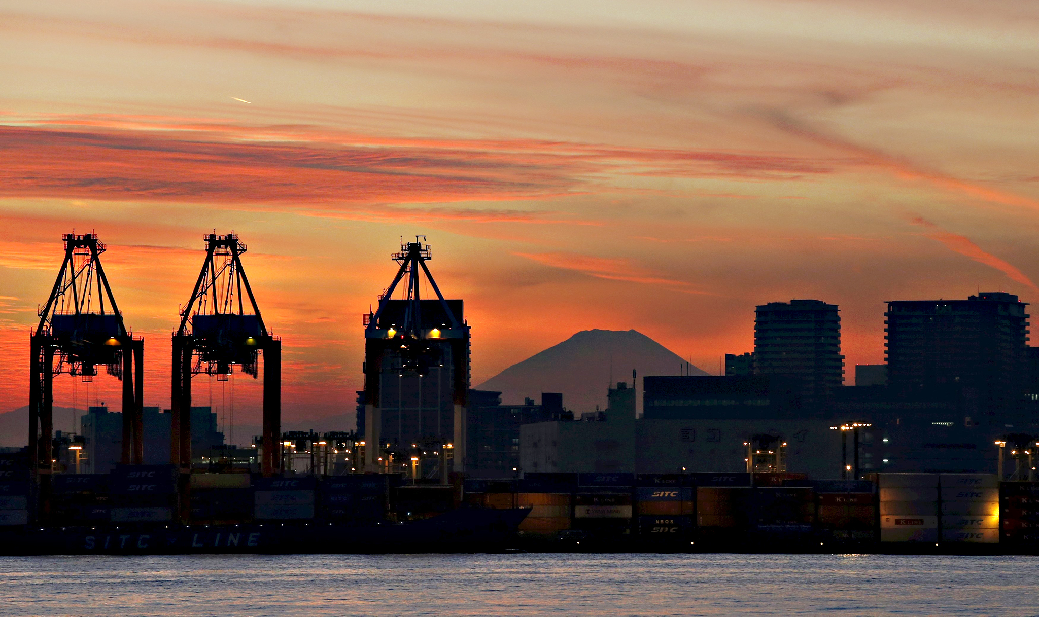 Mount Fuji is seen between cranes and buildings during sunset at a port in Tokyo, Japan, on Wednesday. Japan's core machinery orders unexpectedly jumped in October by the most since March 2014
