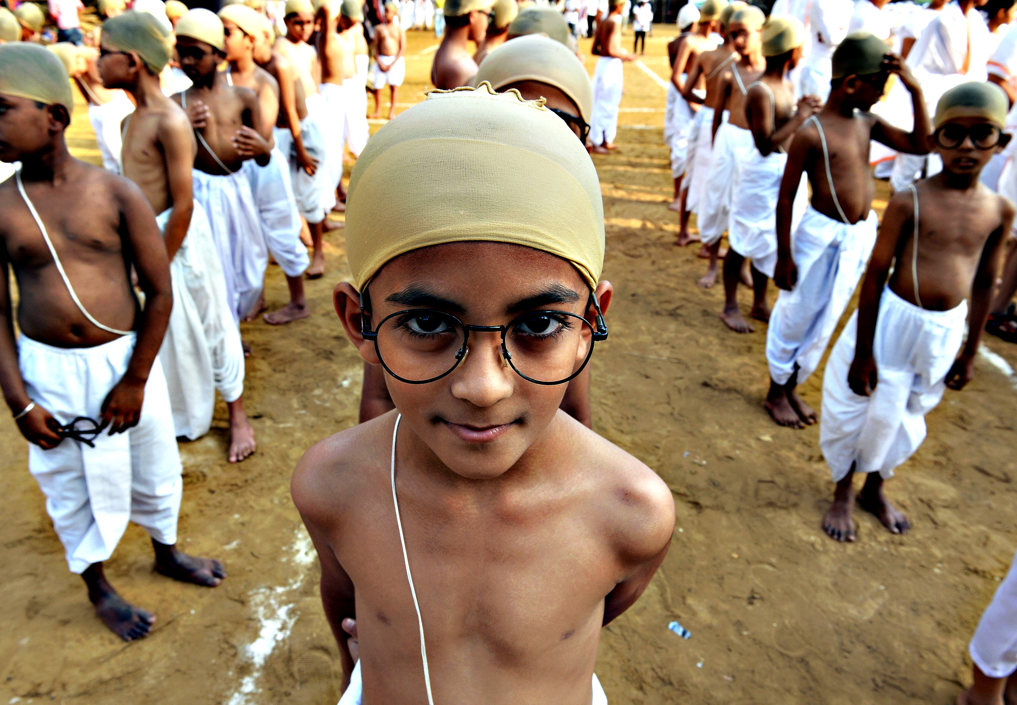 Indian children dressed as the country's founding father Mahatma Gandhi line up for a function in Mumbai on Thursday. Some 1000 children participated in the event promoting the Gandhian ideology to spread the message of simple living, reduce consumption and waste as a mark of respect to Gandhi, famed as the torchbearer of India's fight against British rule