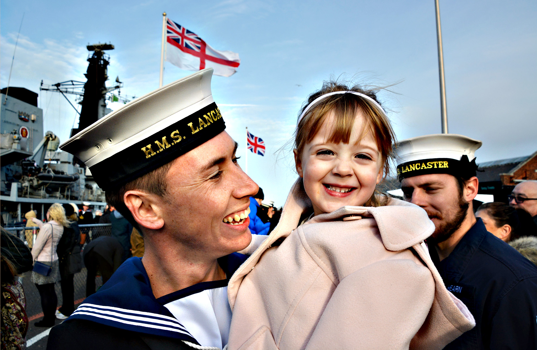 Leading Airman Sam Ashman, 29, from Yeovil, Somerset, with daughter Lexi, as he returns aboard HMS Lancaster to Portsmouth Naval Base after the Royal Navy Frigate completed a 35,000-mile voyage across four oceans. PRESS ASSOCIATION Photo. Picture date: Thursday December 17, 2015