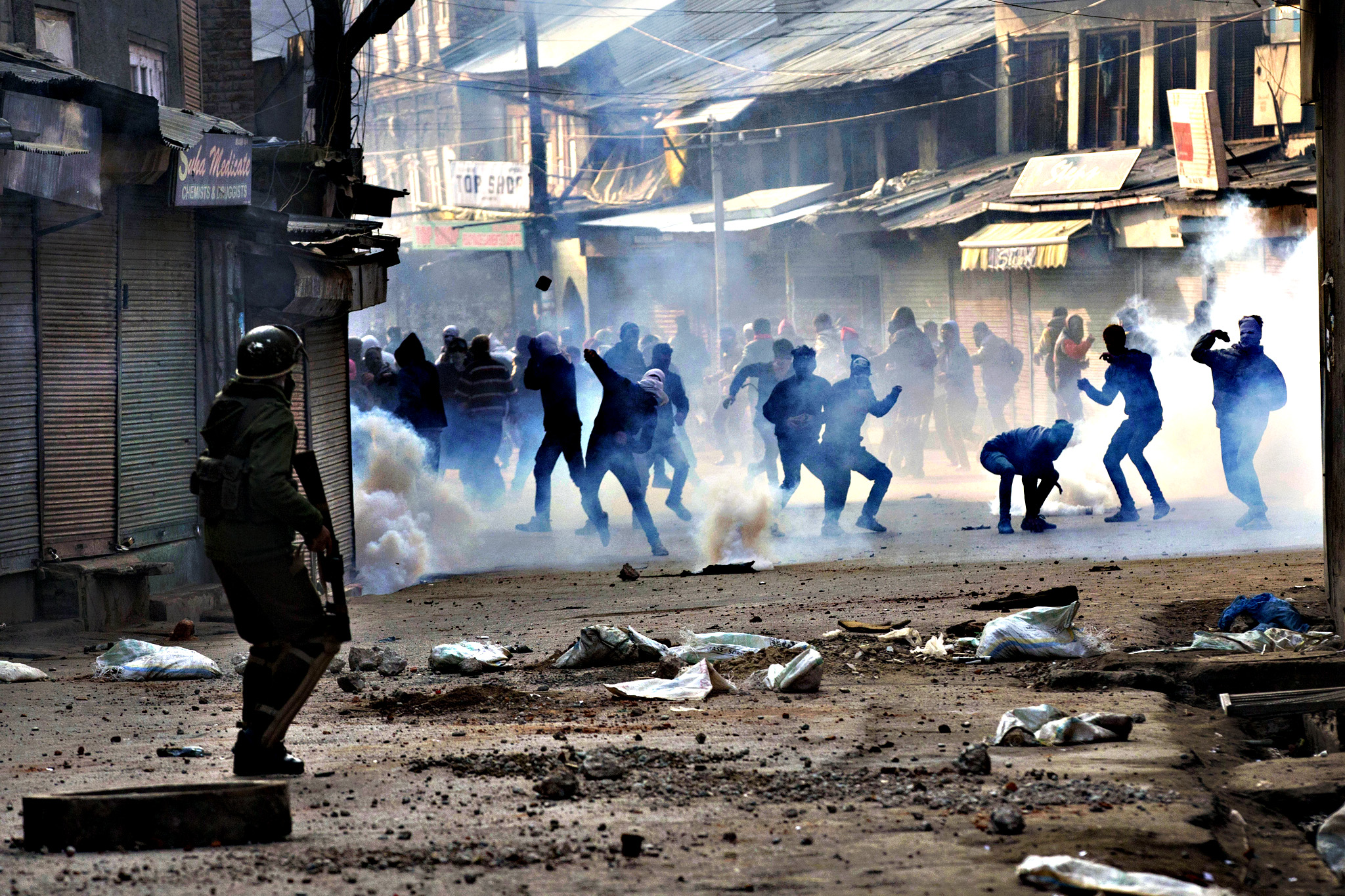 Kashmiri protesters, engulfed in teargas smoke, throw stones at Indian security personnel in Srinagar, Indian-controlled Kashmir, Friday, Dec. 18, 2015. Police fired teargas and rubber bullets to disperse Kashmiris who gathered after Friday afternoon prayers to protest against Indian rule in the disputed region.