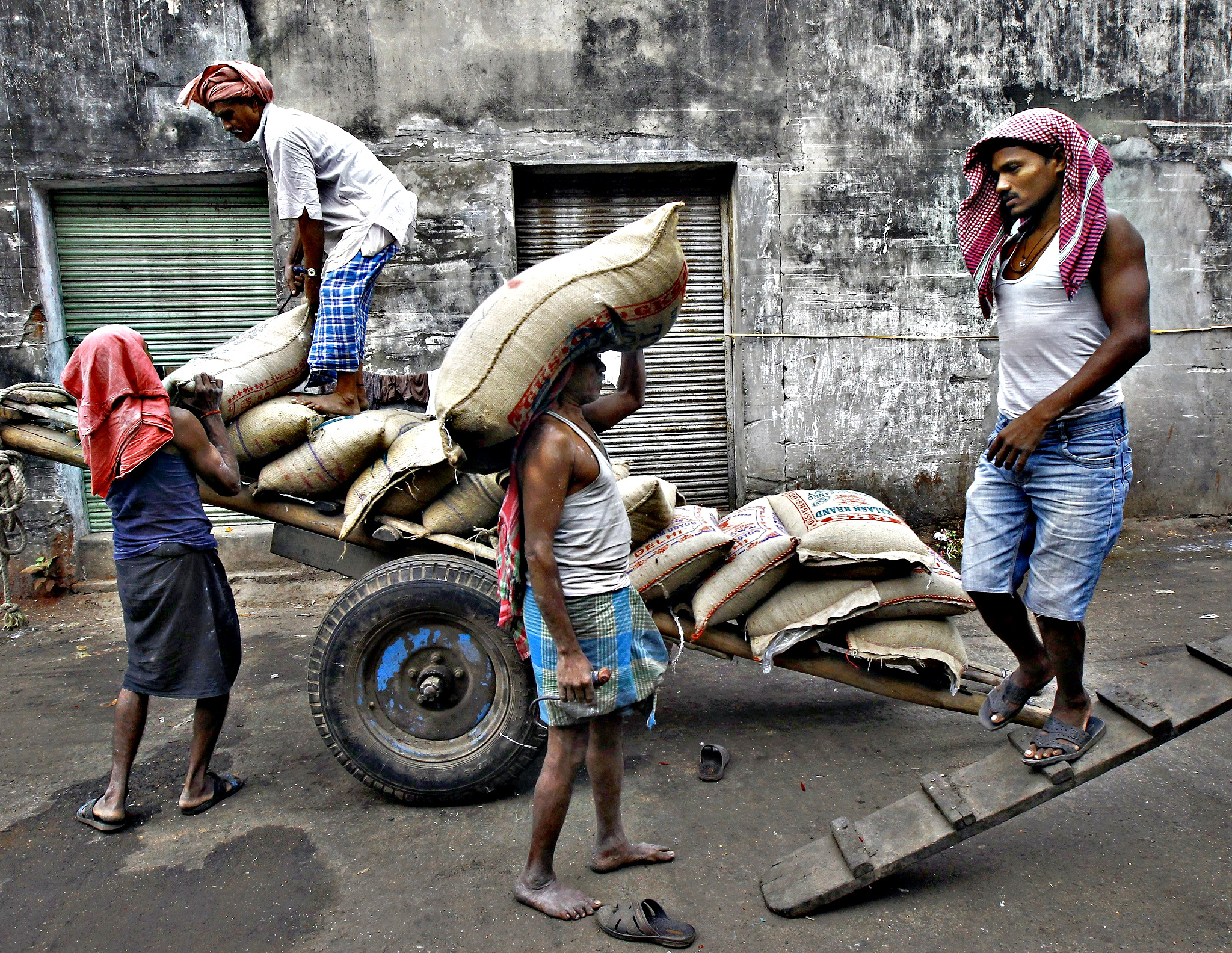 Labourers unload sacks of rice from a handcart at a wholesale market in Kolkata, India, December 14, 2015. India's wholesale prices fell for a 13th straight month in November, but a sharp pickup in food prices and a pending wage hike for millions of government employees are likely to keep policymakers worried about potential inflationary risks.