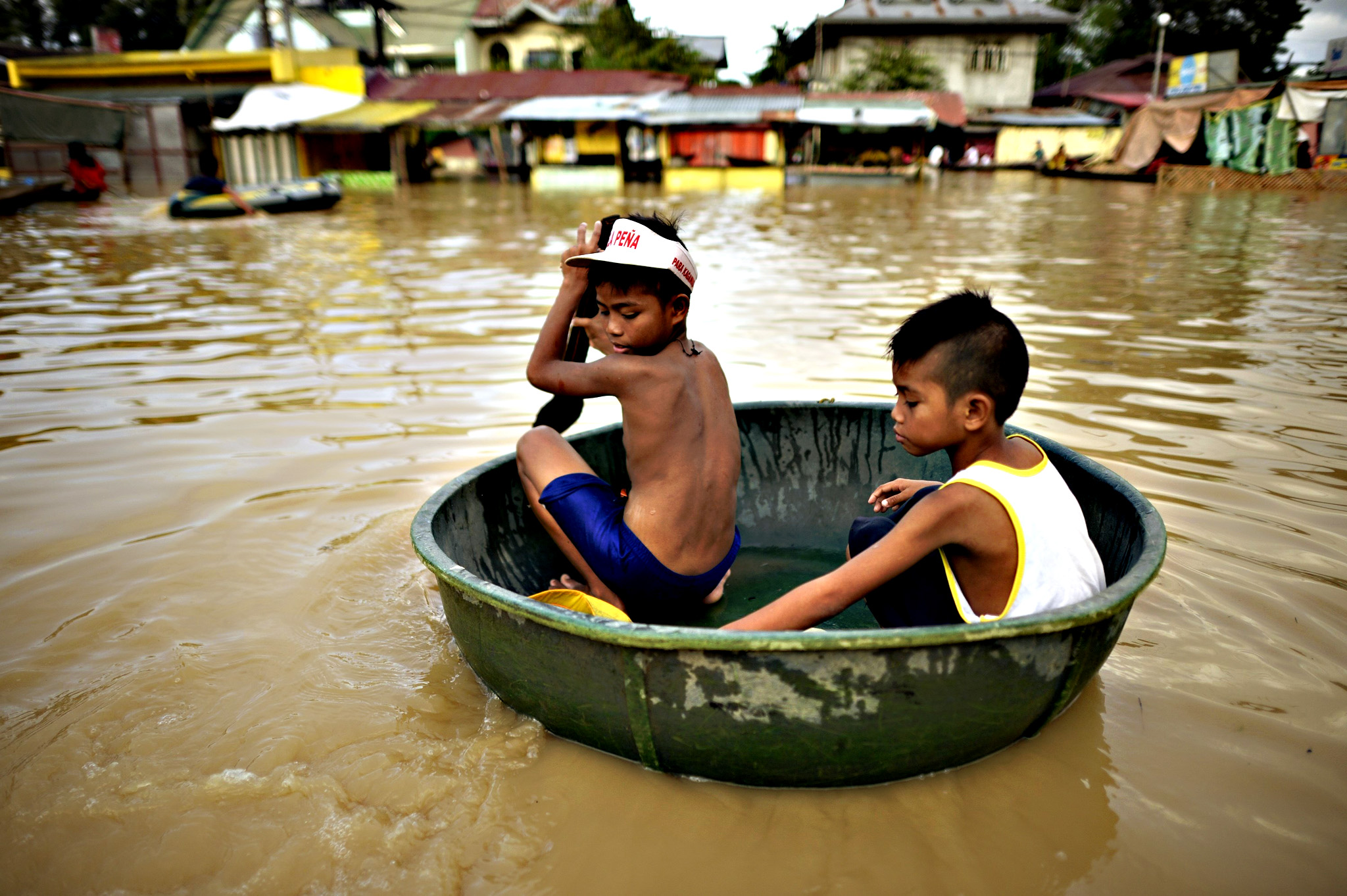 Children commute in a water basin at a flooded market in Candaba, Pampanga, north of Manila on Friday. Vast swathes of farmlands inundated by Typhoon Koppu in October were flooded again this week by rains from Typhoon Melor and the flooding could worsen or spread to other areas as a second storm in less than a week threatens the country.
