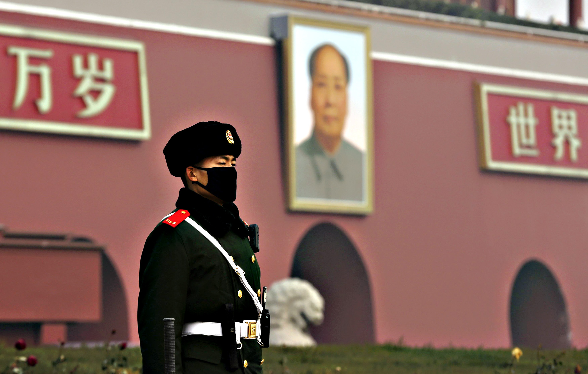 "A paramilitary policeman wearing a mask stands guard in front of the giant portrait of Chinese late chairman Mao Zedong, amid heavy smog after the city issued its first ever ""red alert"" for air pollution in Beijing, China, December 9, 2015. Picture taken December 9, 2015."